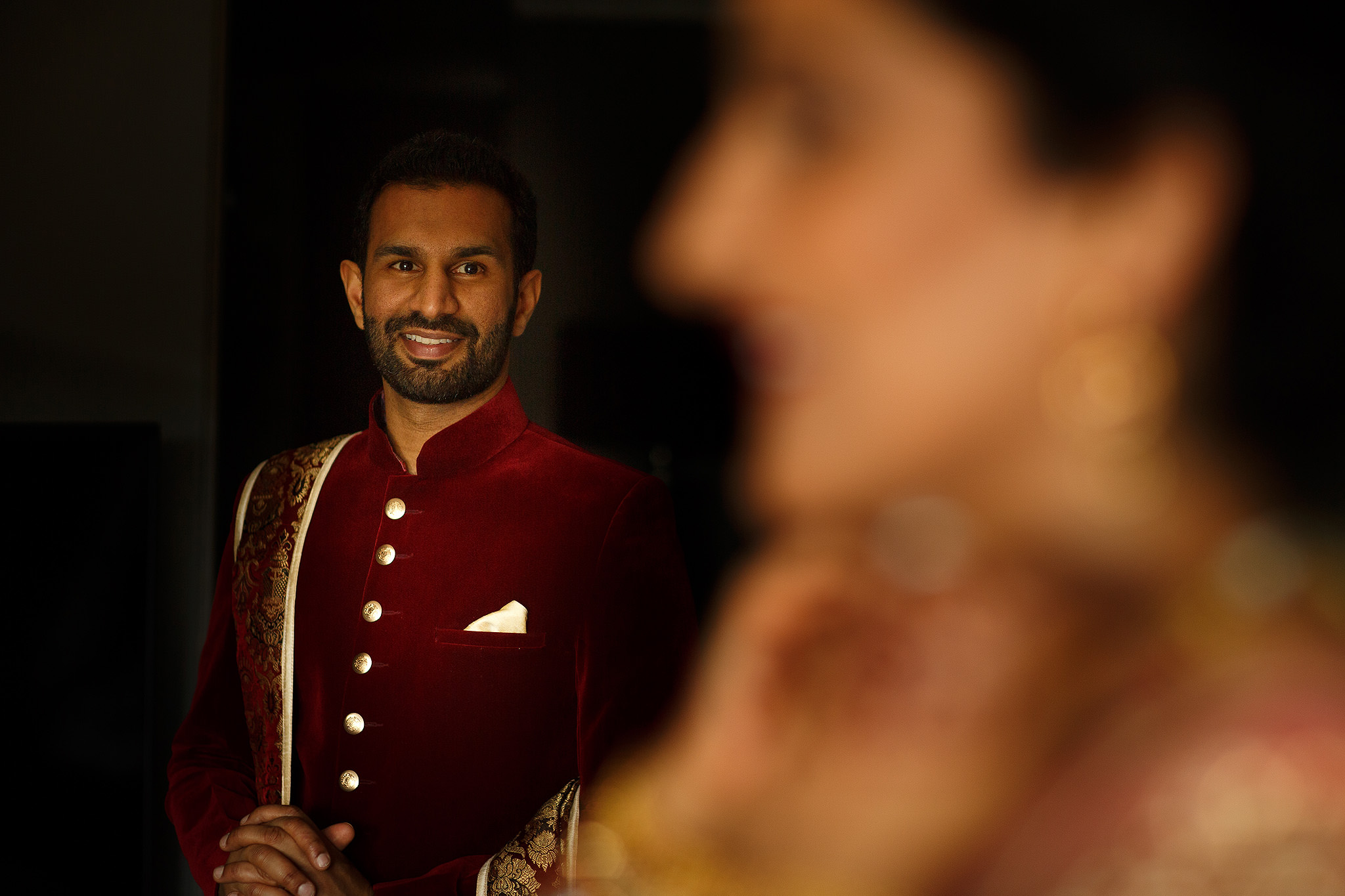 Indian groom looking at bride as she makes finishing touches