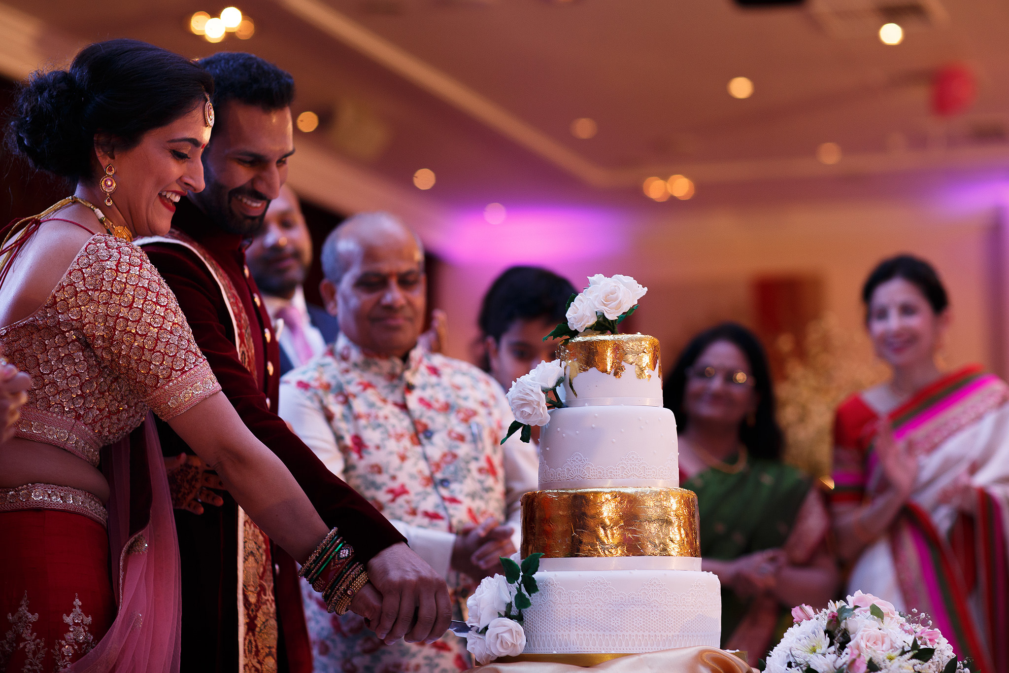 Indian bride and groom cutting the cake on the dancefloor