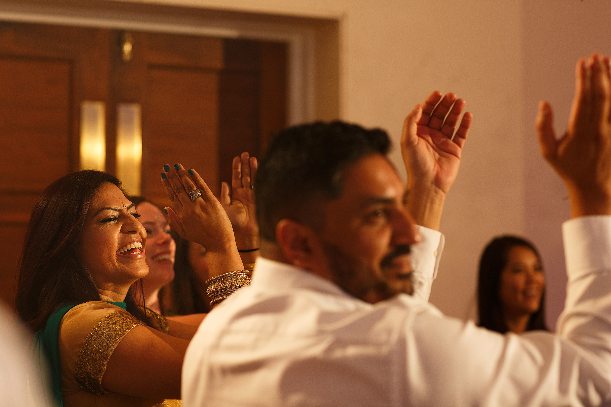 Guests laughing during speeches at Indian wedding reception