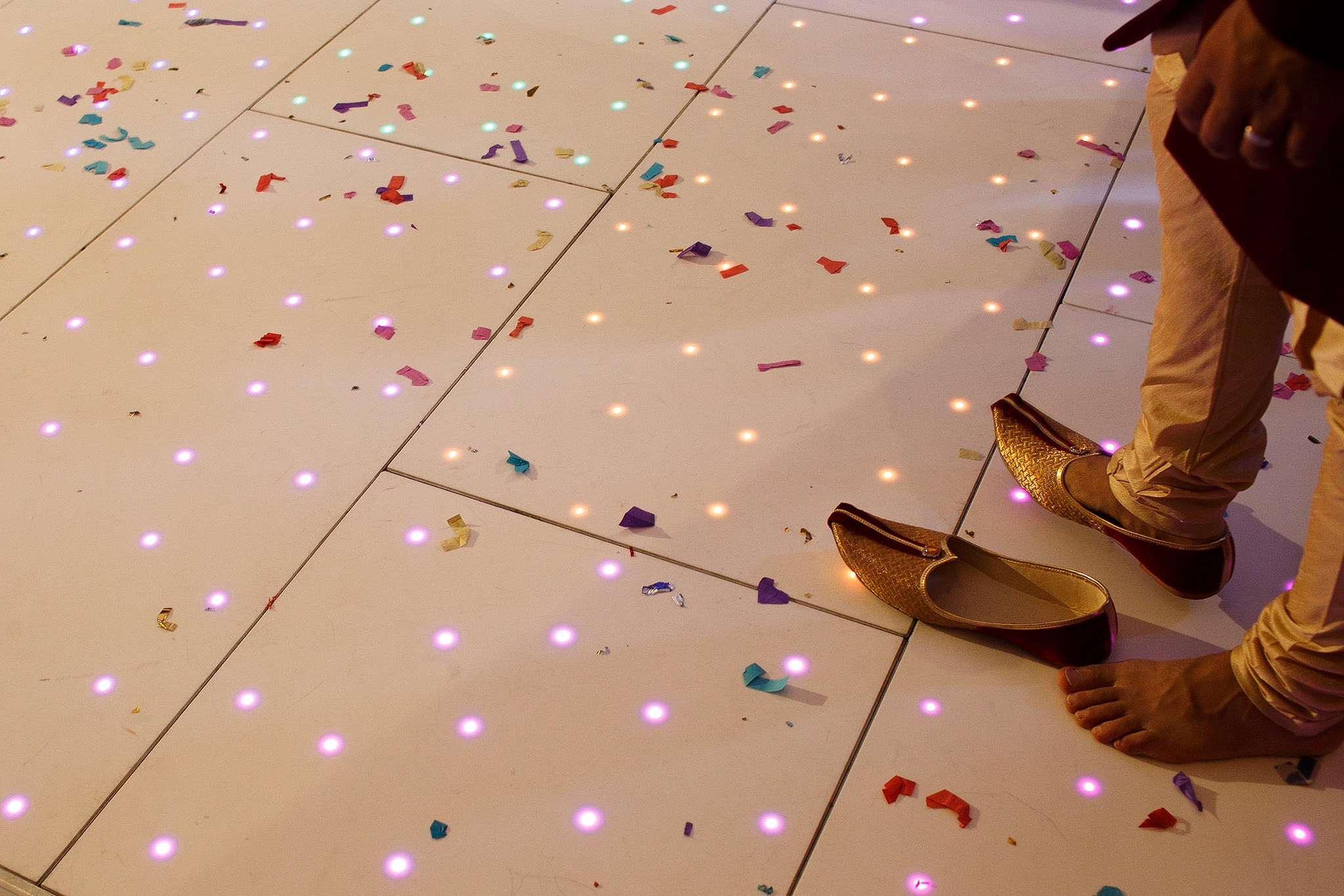 Indian groom removed shoes on the dance floor at wedding reception