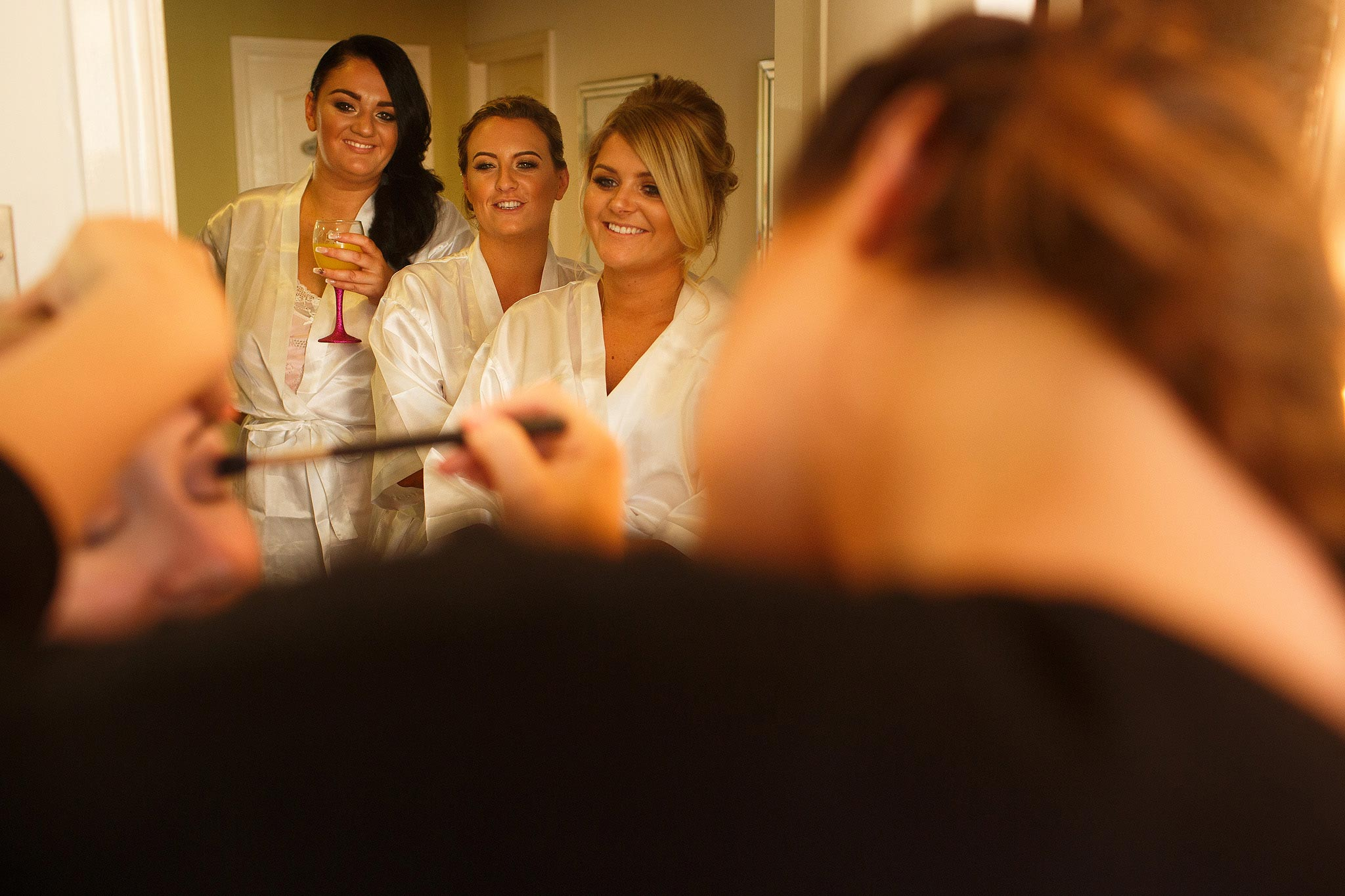 Bride having make up applied whilst bridesmaids are laughing in the background