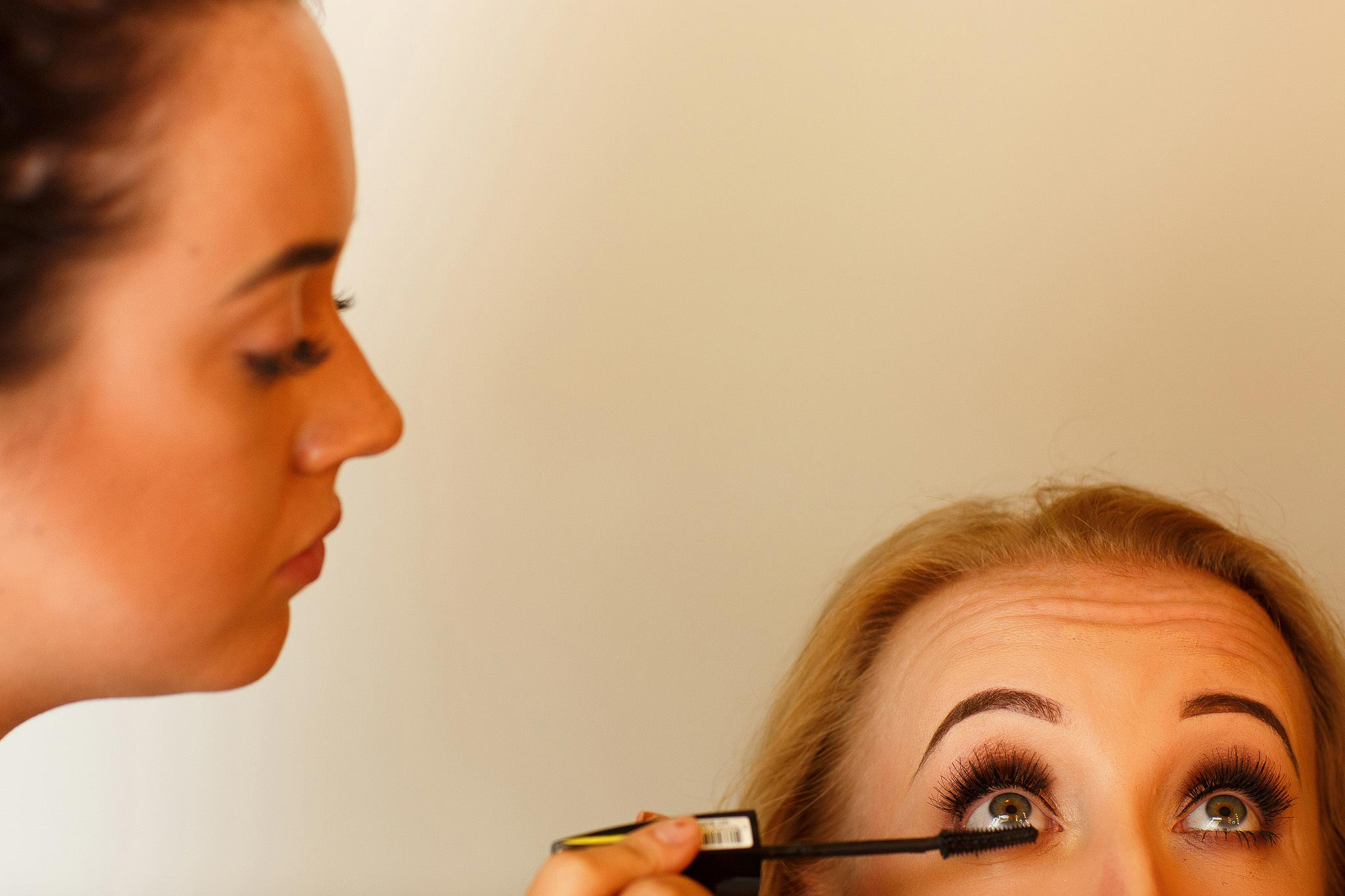 Creative wedding photograph of bride having make up applied