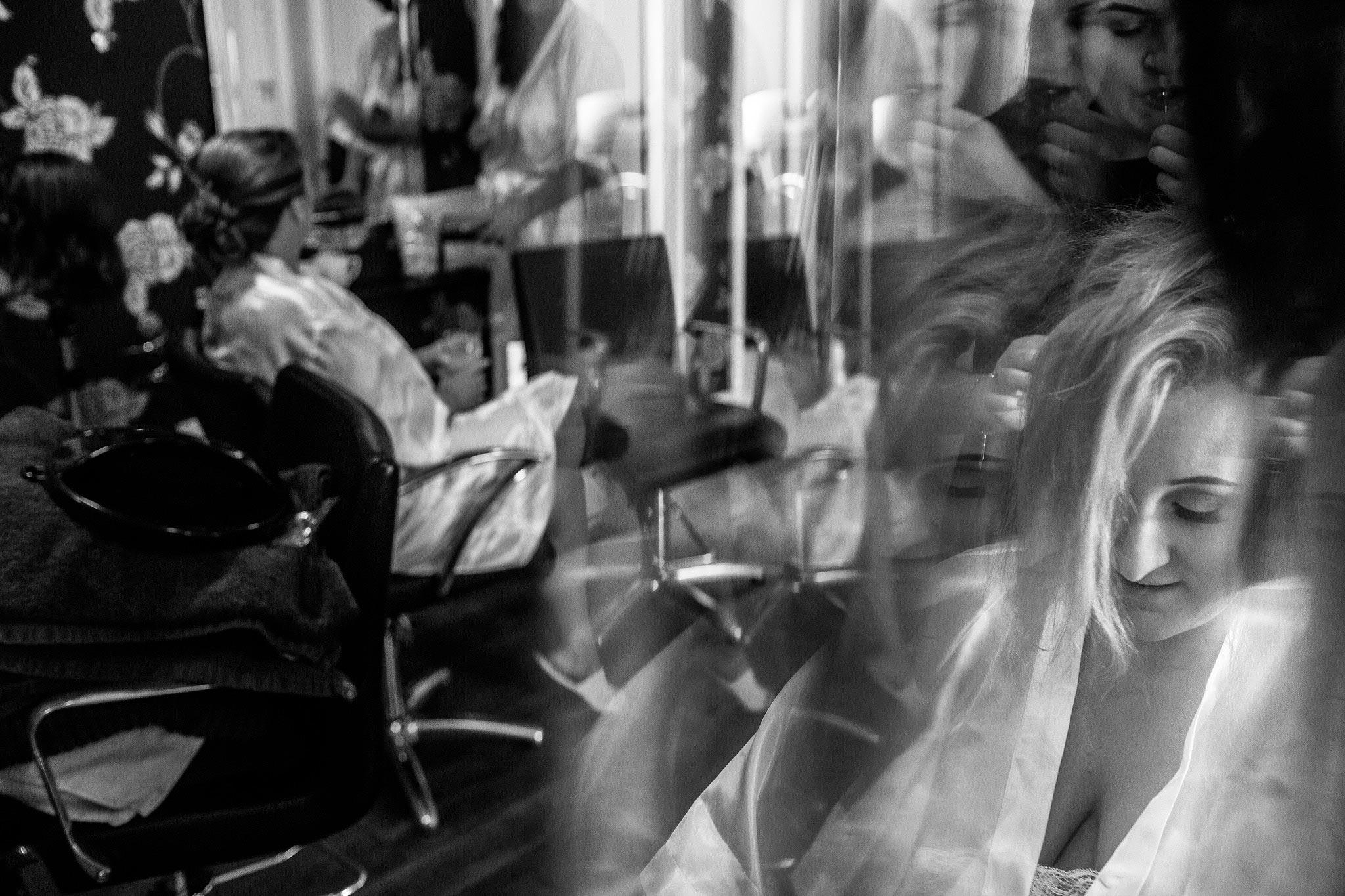 Creative wedding photograph of bride having make up applied
