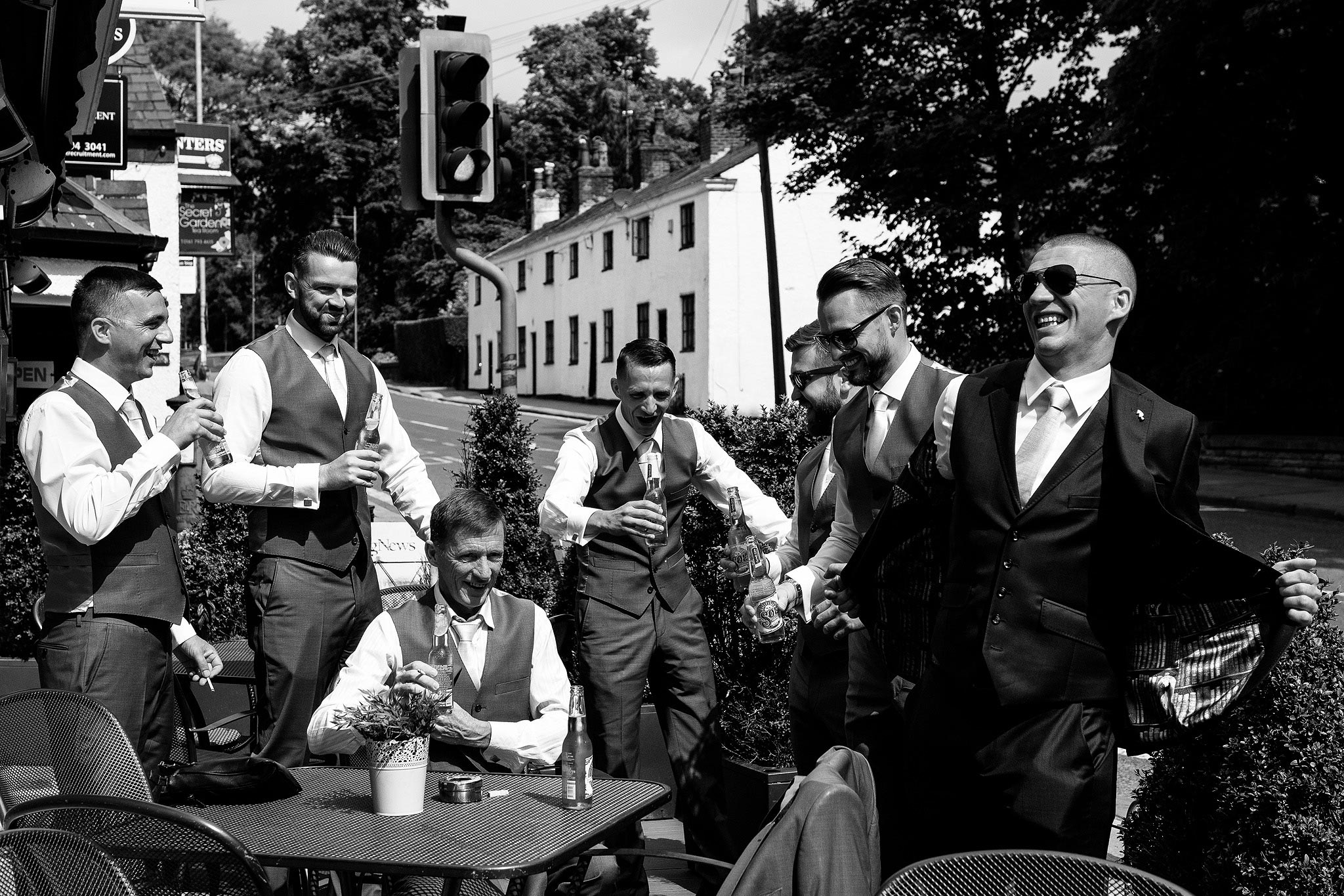 Black and white photograph of a groom enjoying a drink with his friends