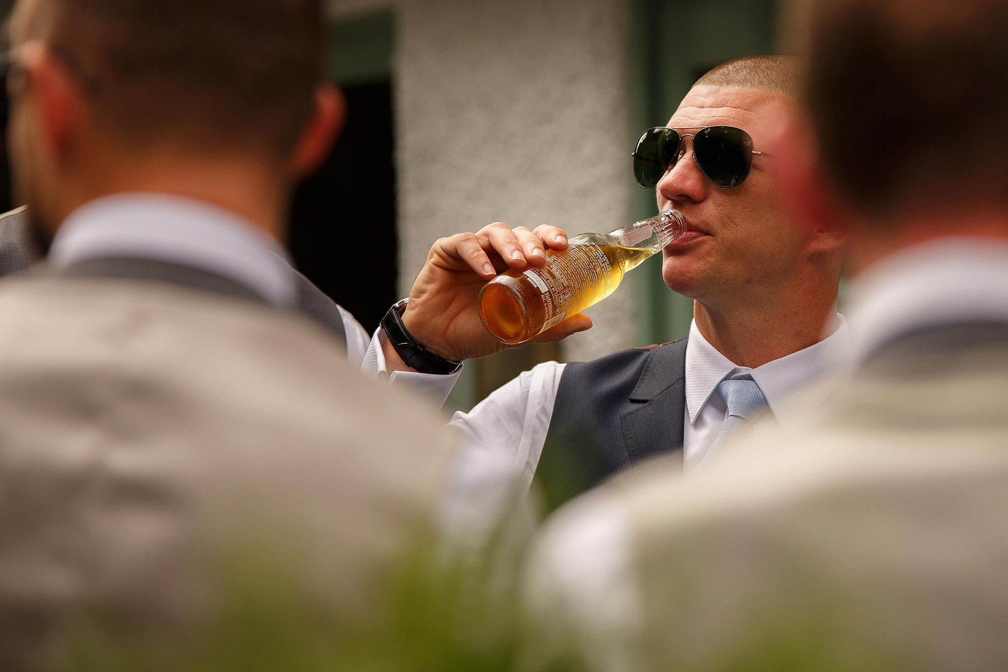 Photograph of a groom enjoying a drink with his friends