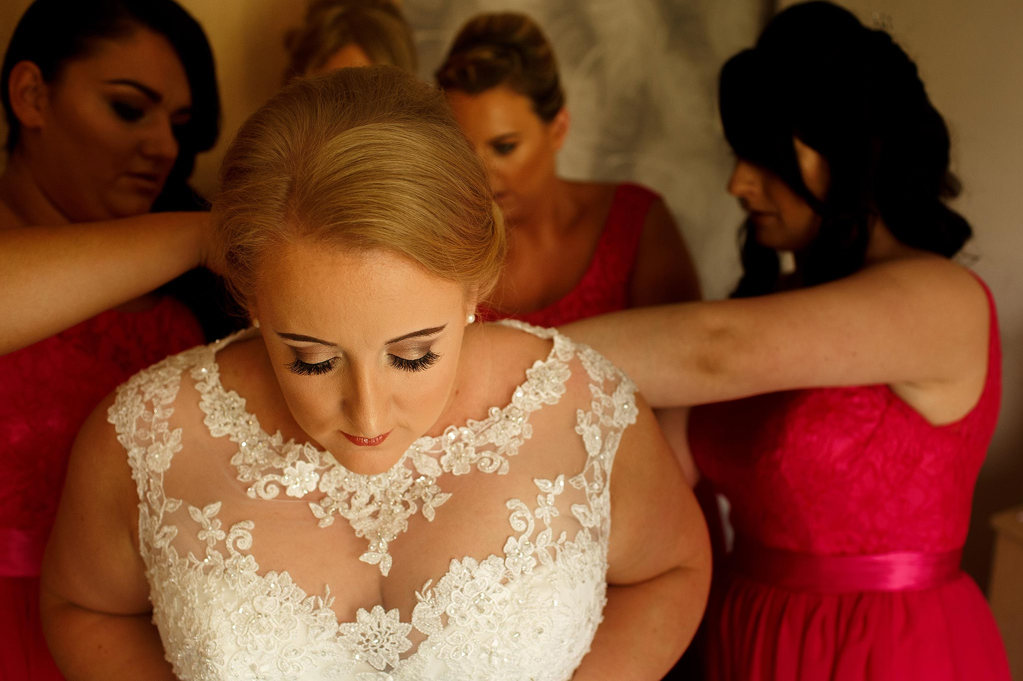 Photograph of a bride with her eyes closed as her bridesmaids fasten her dress.