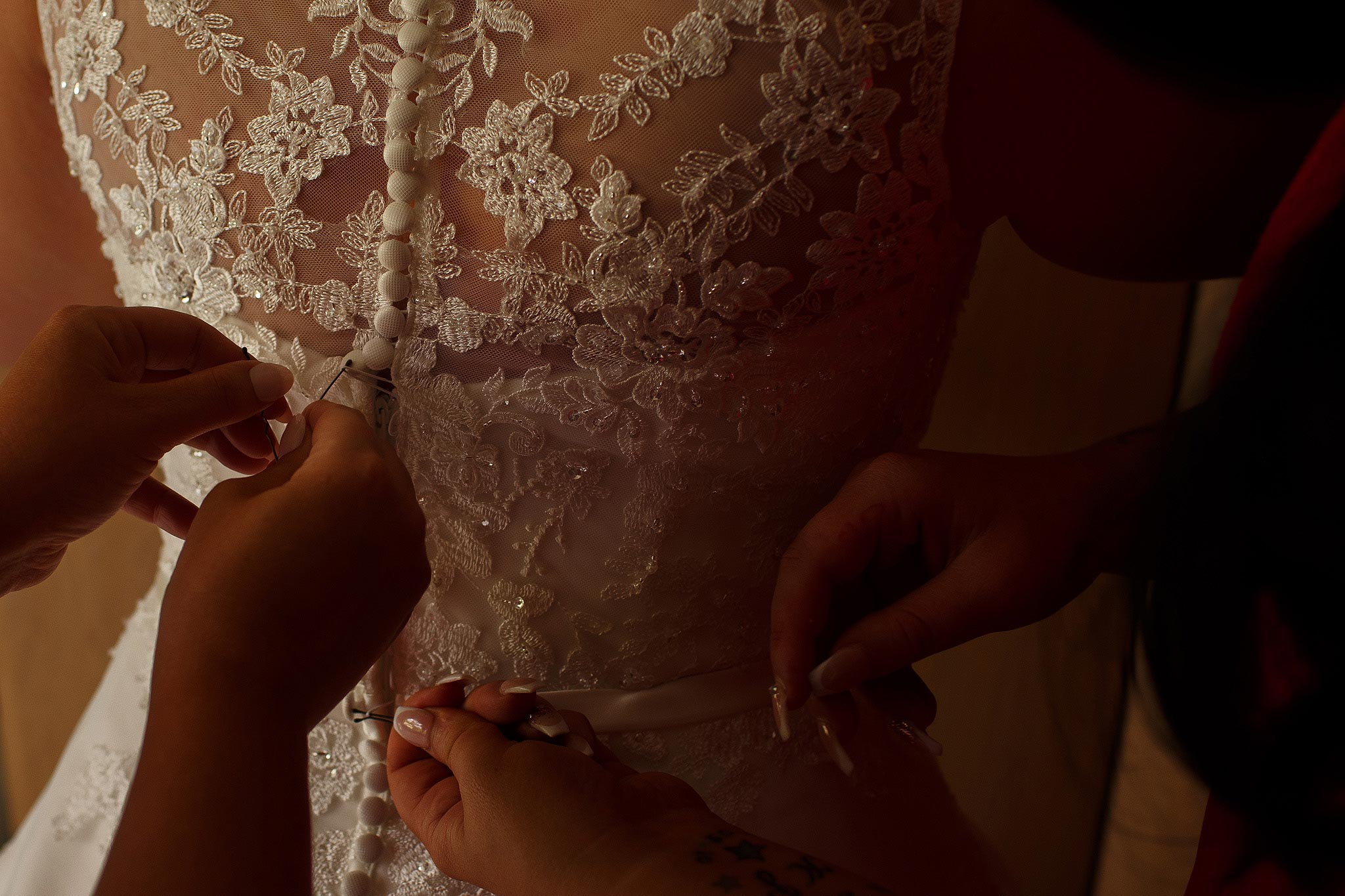 Close up photograph of hands fastening a brides dress