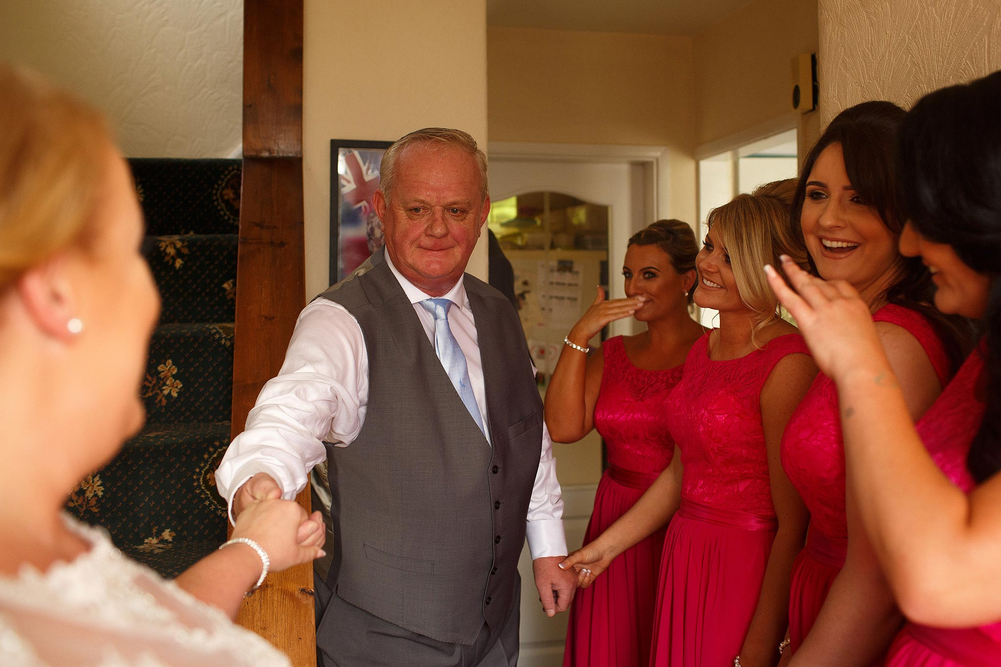 The reactions of bridesmaid and father of the bride as the bride walks down the aisle.