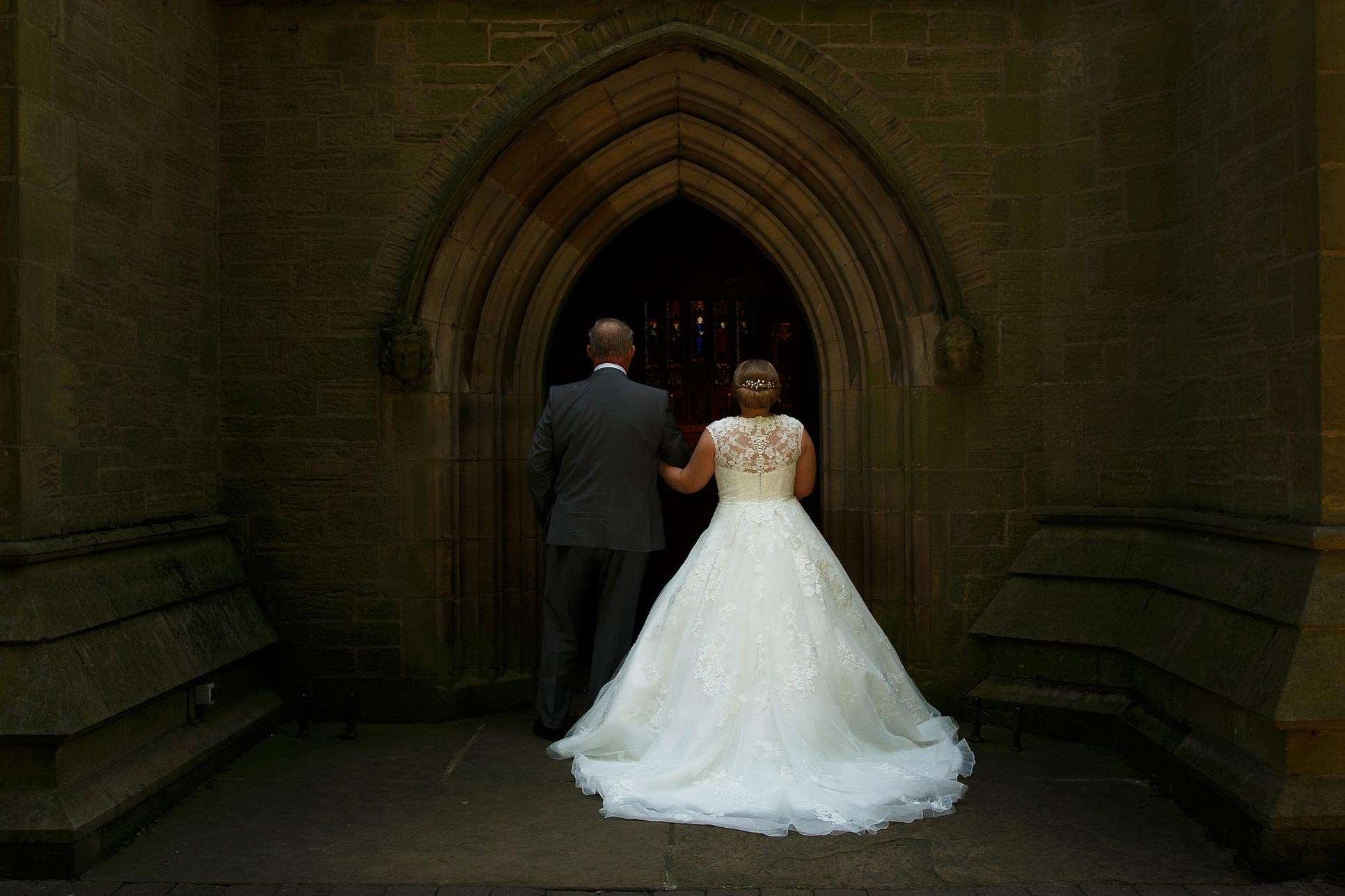 Bride and her father from behind as they enter St Marks Church Manchester