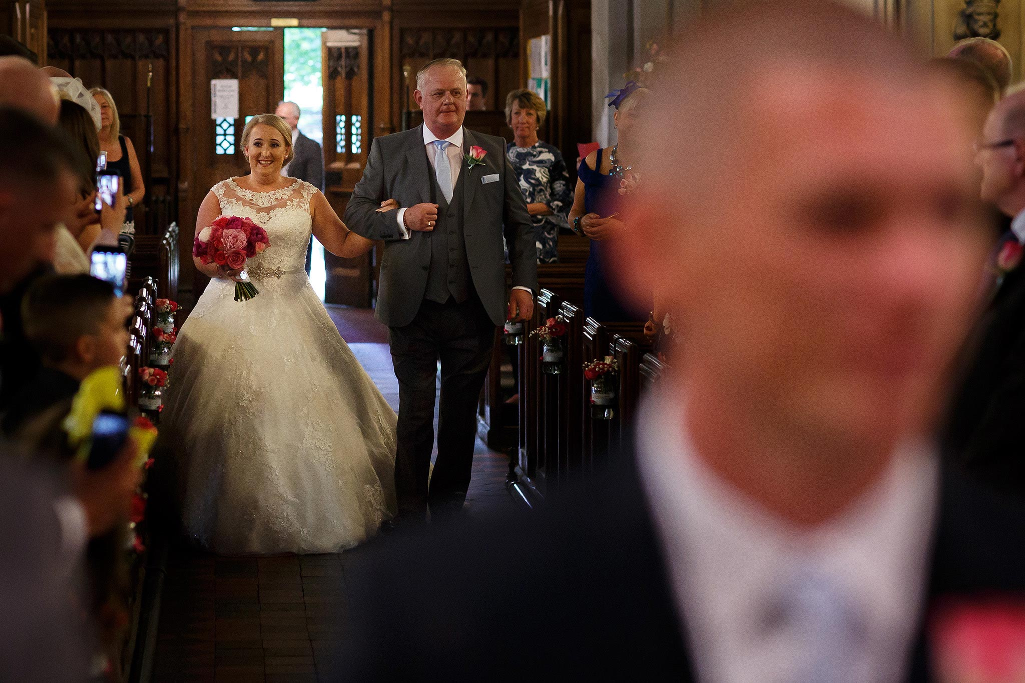 Bride and father of the bride walking down the aisle.