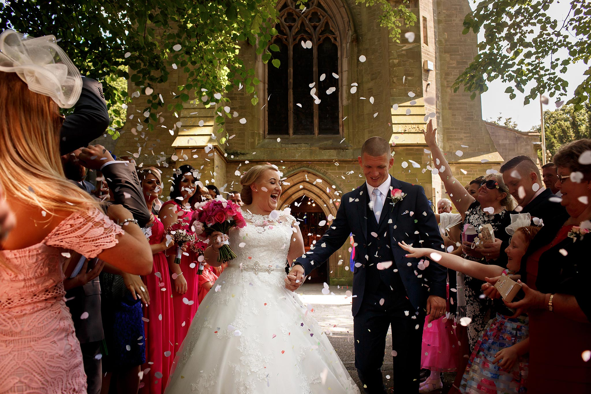 Bride and groom walking out under confetti at St Marks Church
