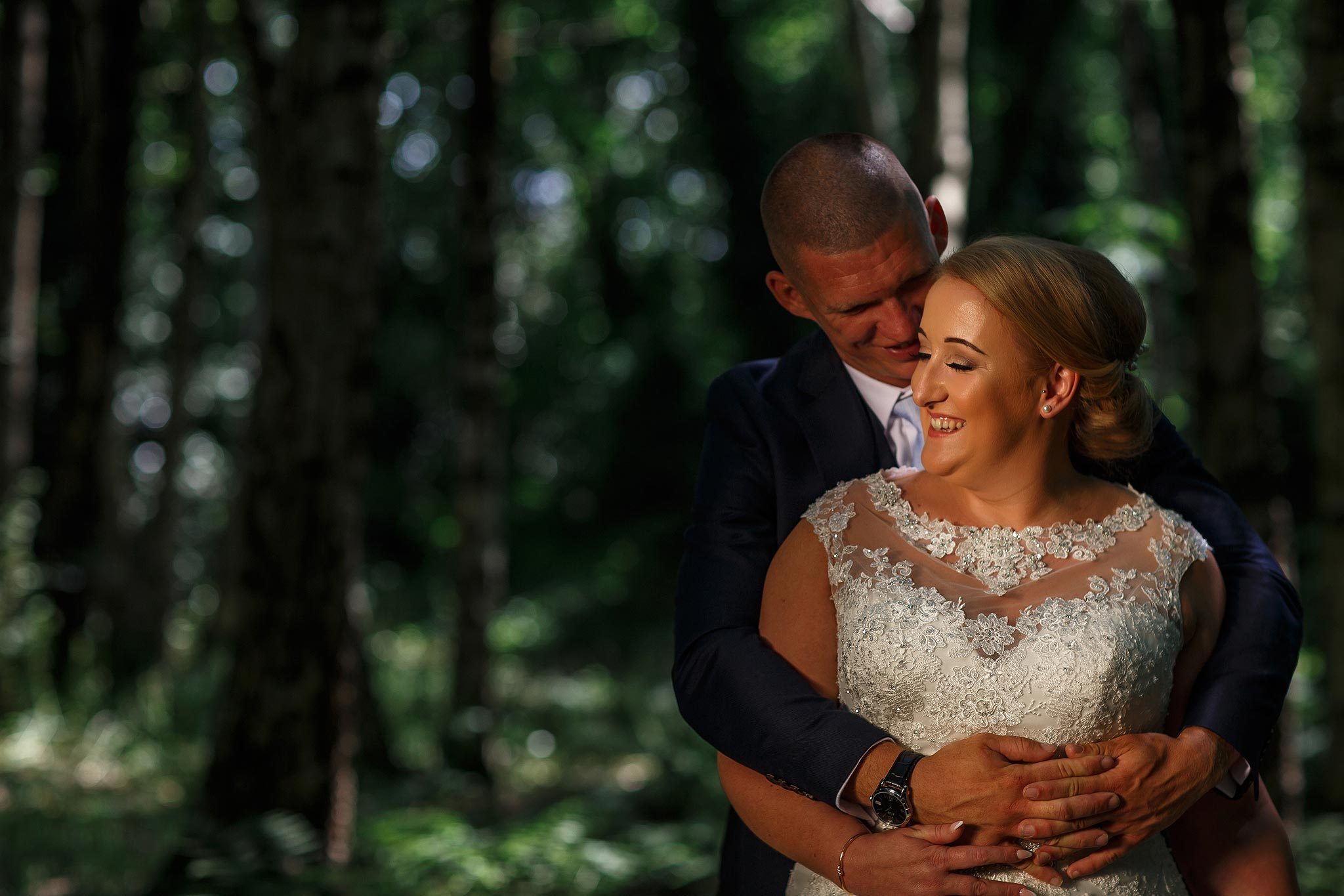 Bride and groom in woodland under direct sunlight