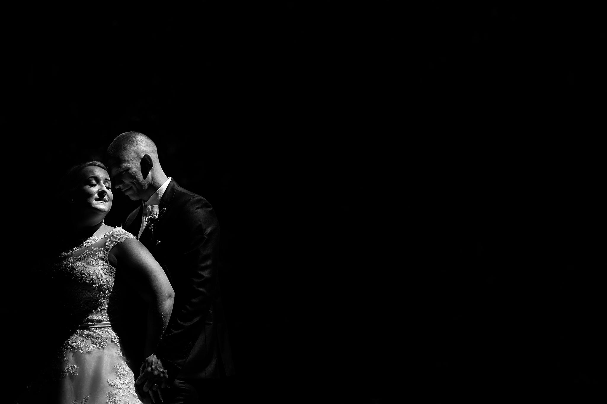 Black and white portrait of bride and groom in direct sunlight