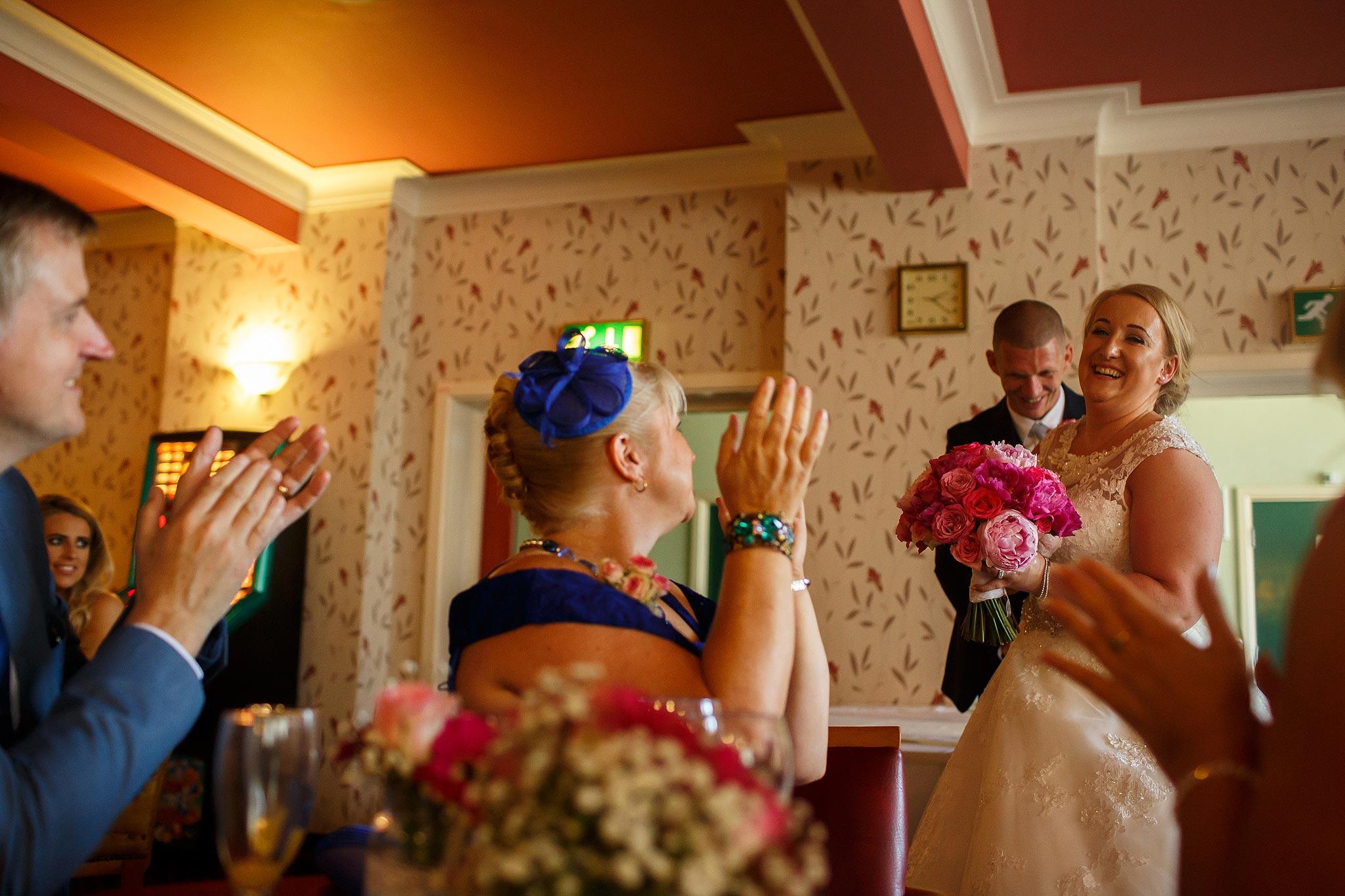 Bride and groom walking into their reception at Swinton Masonic Hall