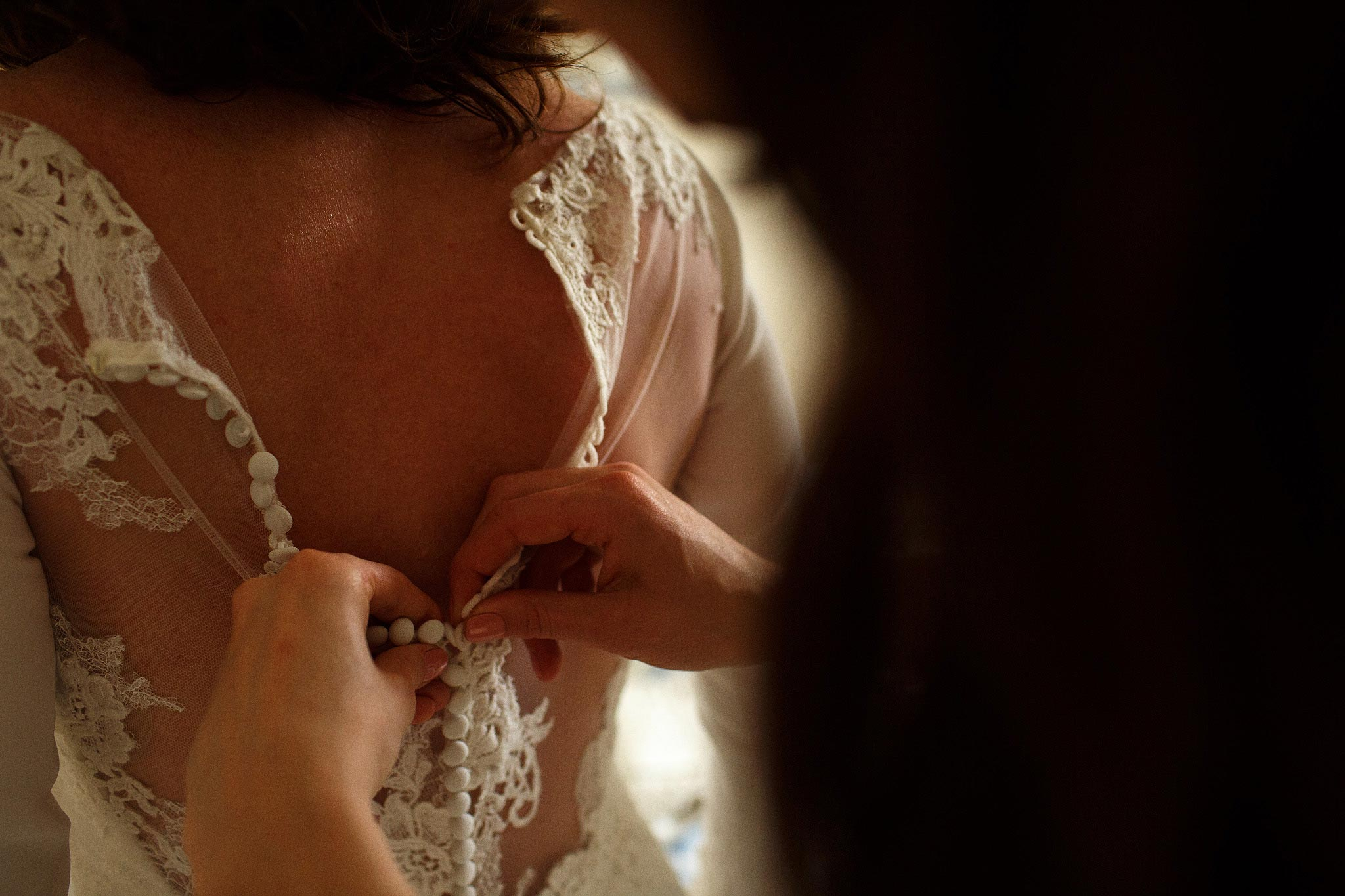 close up of bride having her dress fastened up