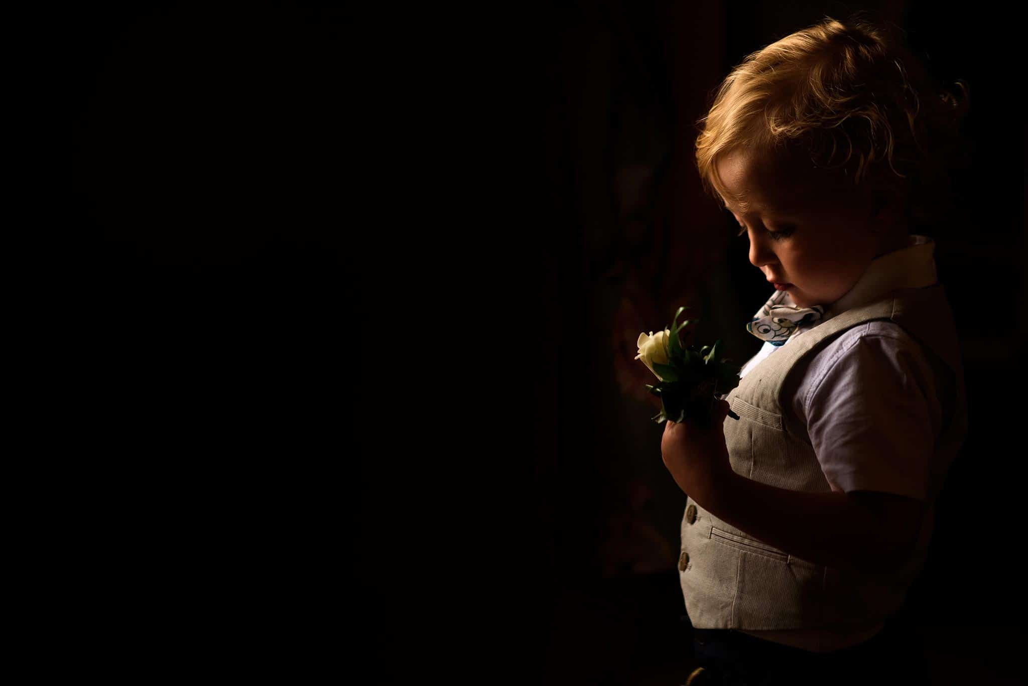 page boy looking at buttonhole in gorgeous light