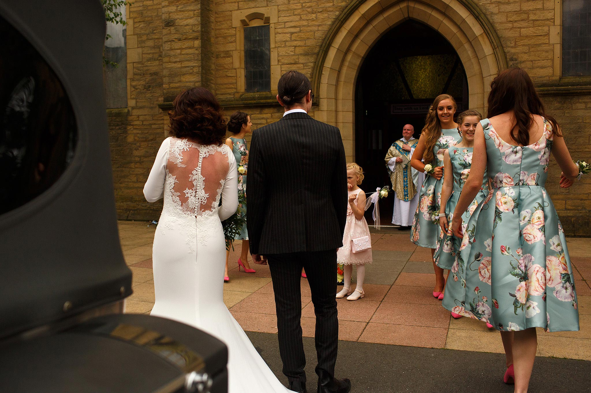 bride being escorted into church as the wedding party watch