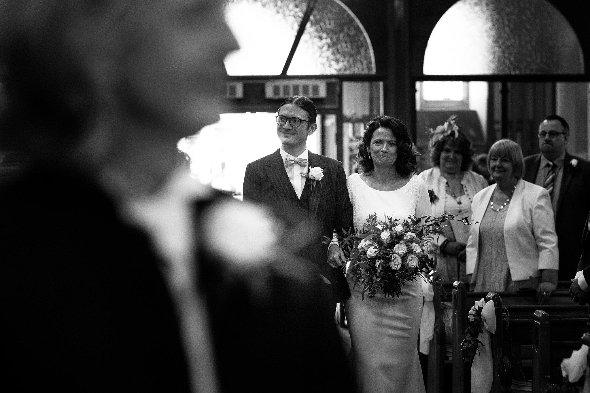 bride being walked down the aisle by her son