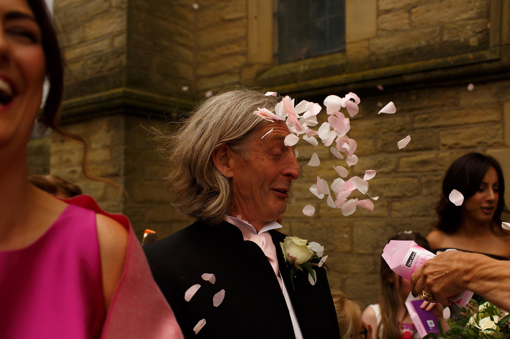 Confetti being thrown directly in grooms face