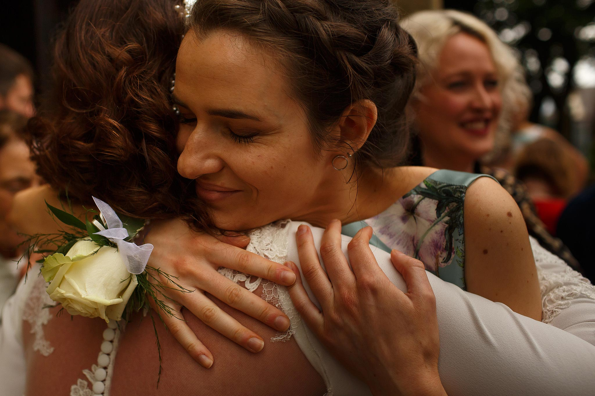 Bridesmaid hugging bride outside church
