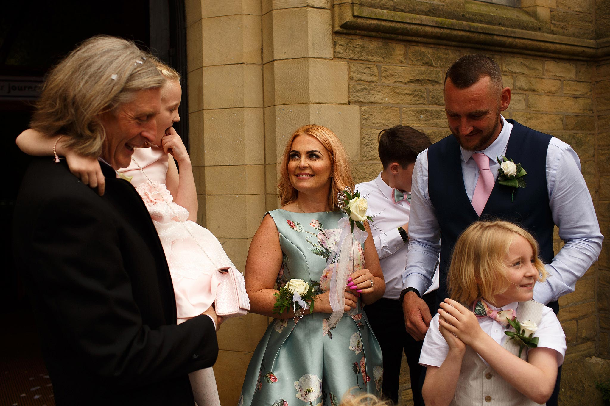 Wedding guests laughing outside church in Lancashire