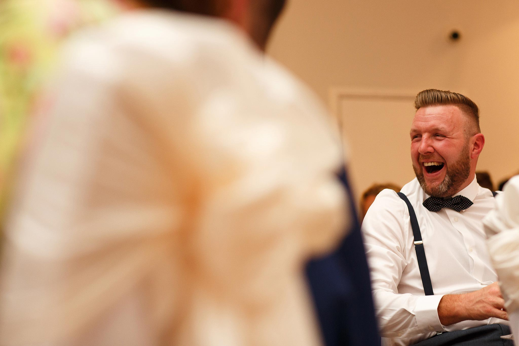 Guest laughing during speeches at Stirk House wedding reception