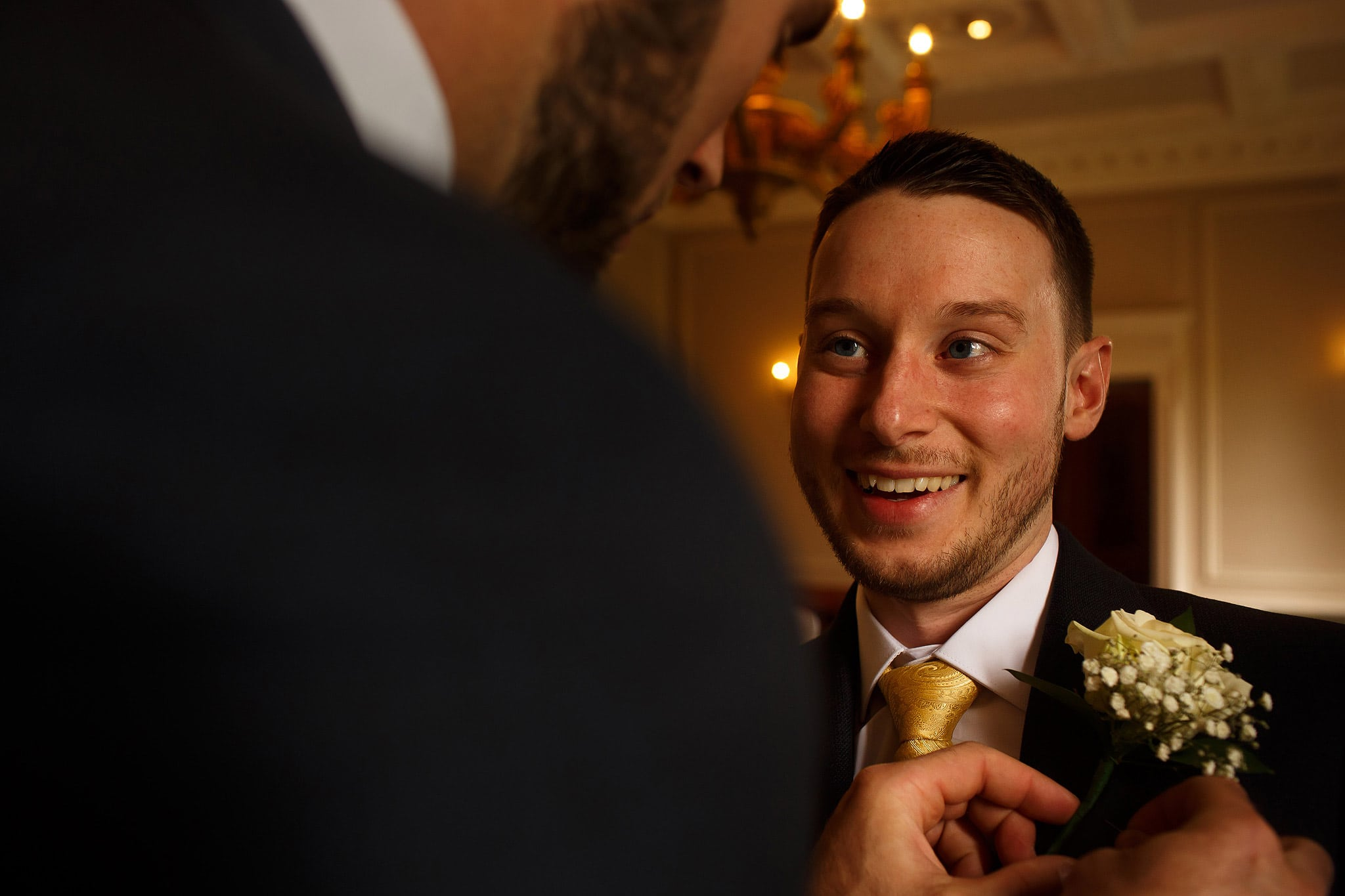 Groom laughing wearing mustard tie as he has button hole pinned