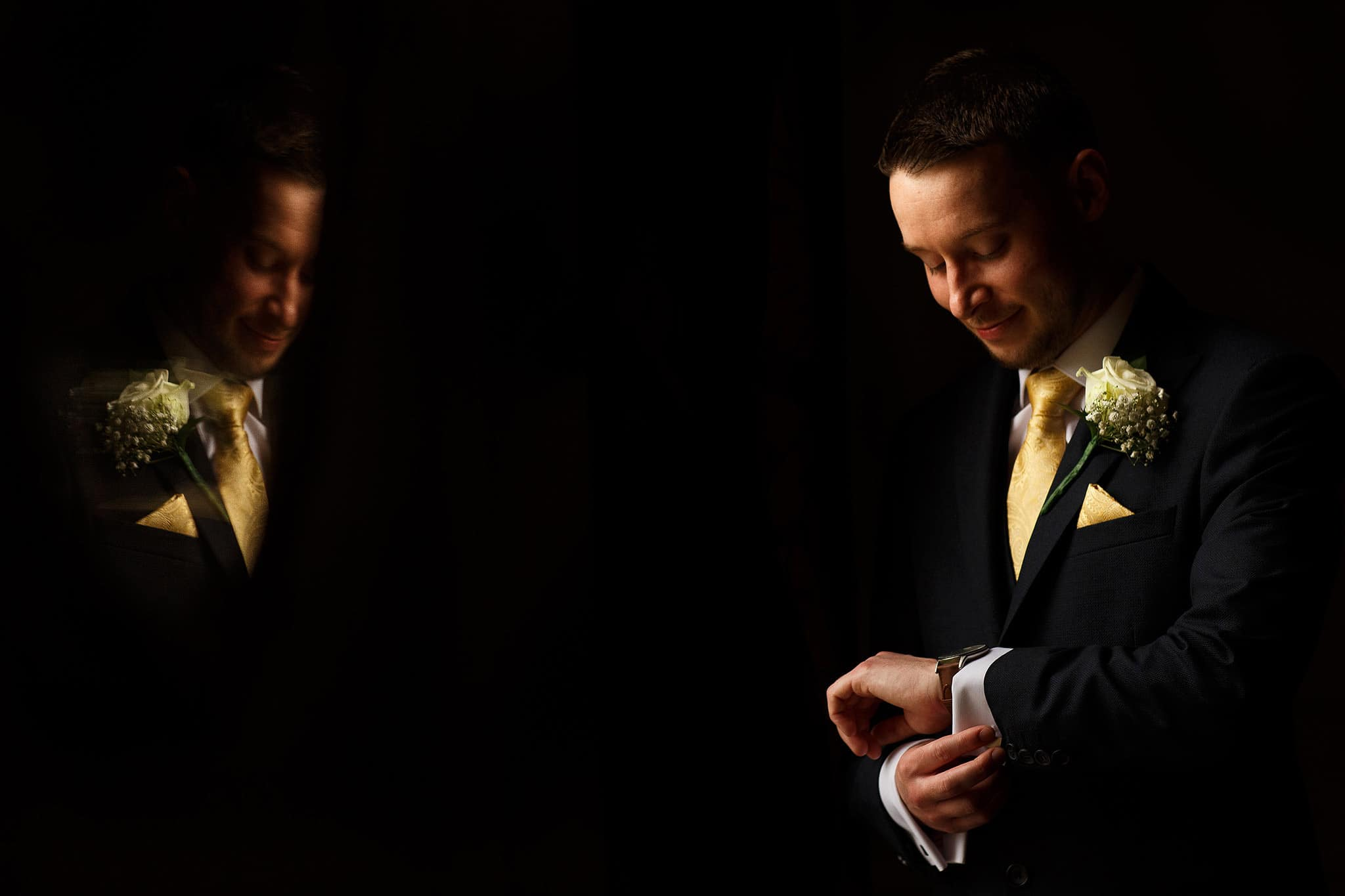 groom looking at new watch in perfect window light inside Crathorne Hall
