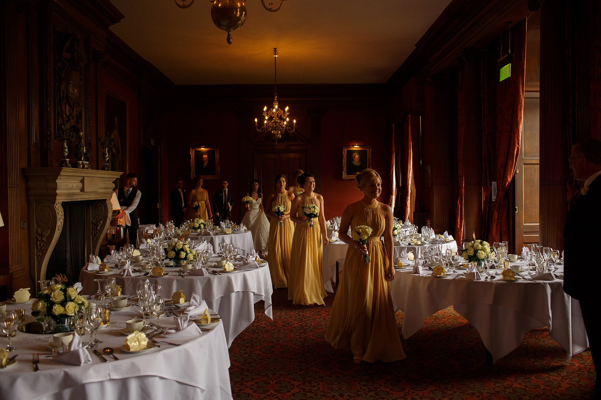 Bridesmaids all wearing gold dresses entering wedding ceremony at Crathorne Hall