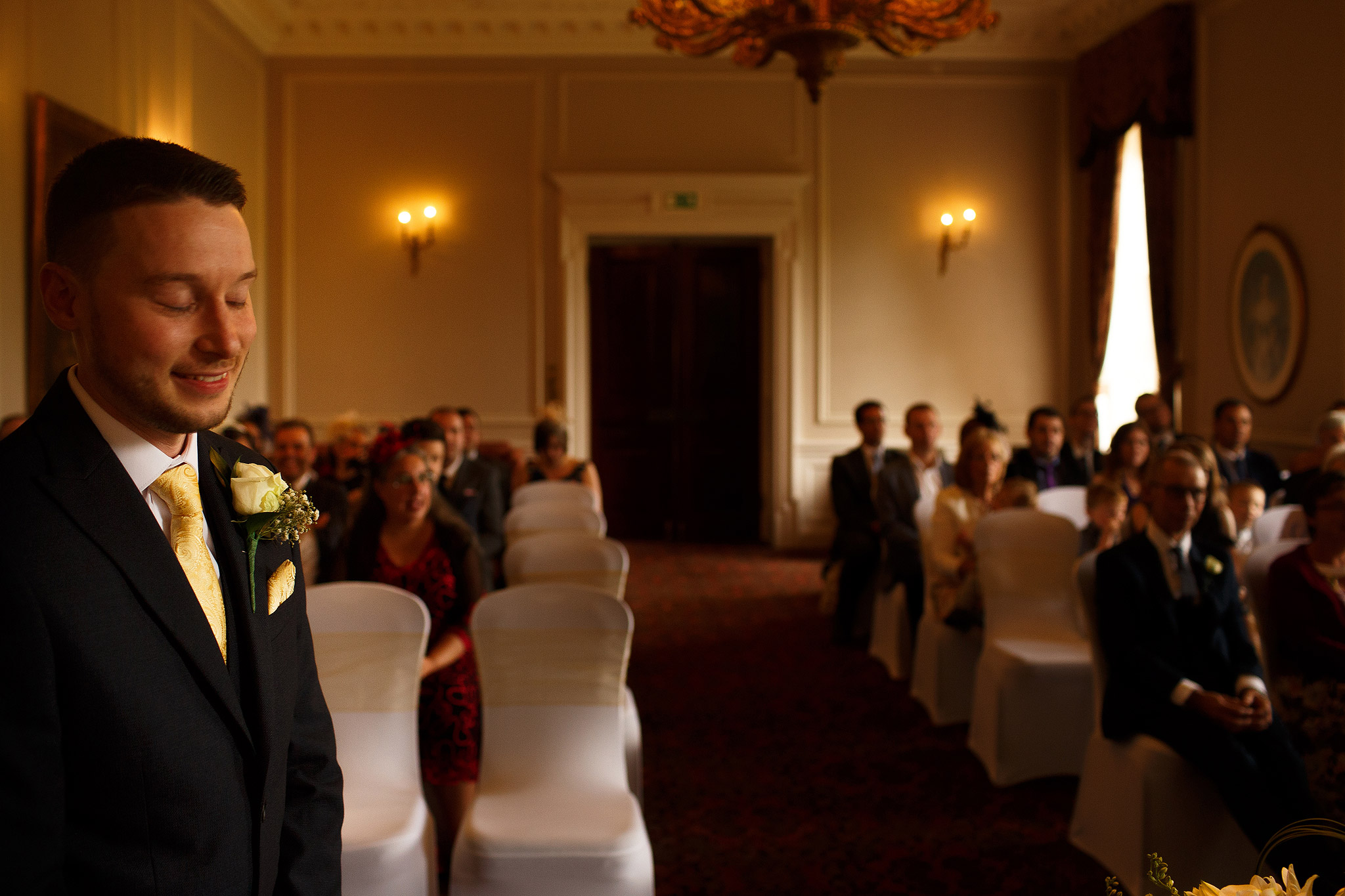 Groom looking nervous at the top of the aisle inside Crathorne Hall
