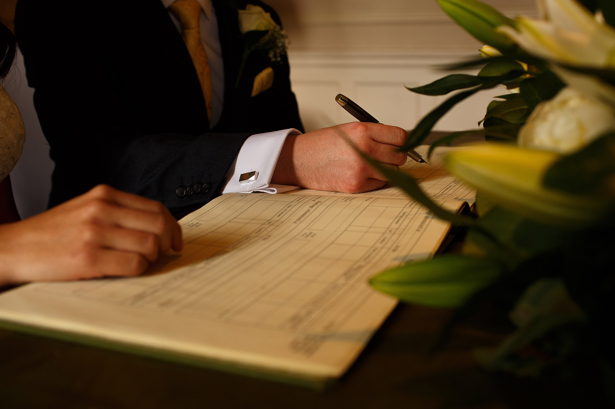Bride and groom signing register at Crathorne Hall wedding ceremony