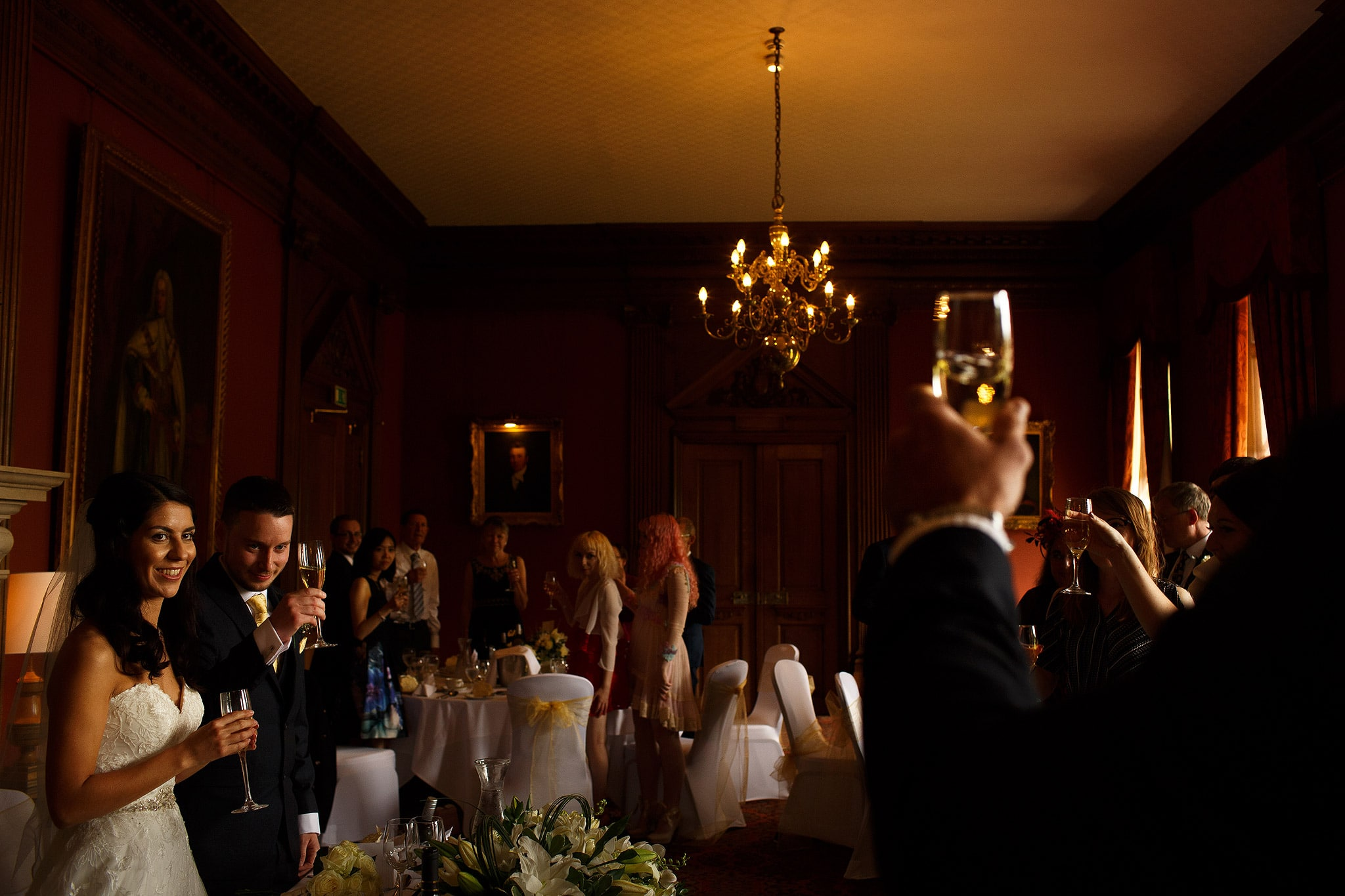 Wedding guests raising glasses to cheers at Crathorne Hall wedding