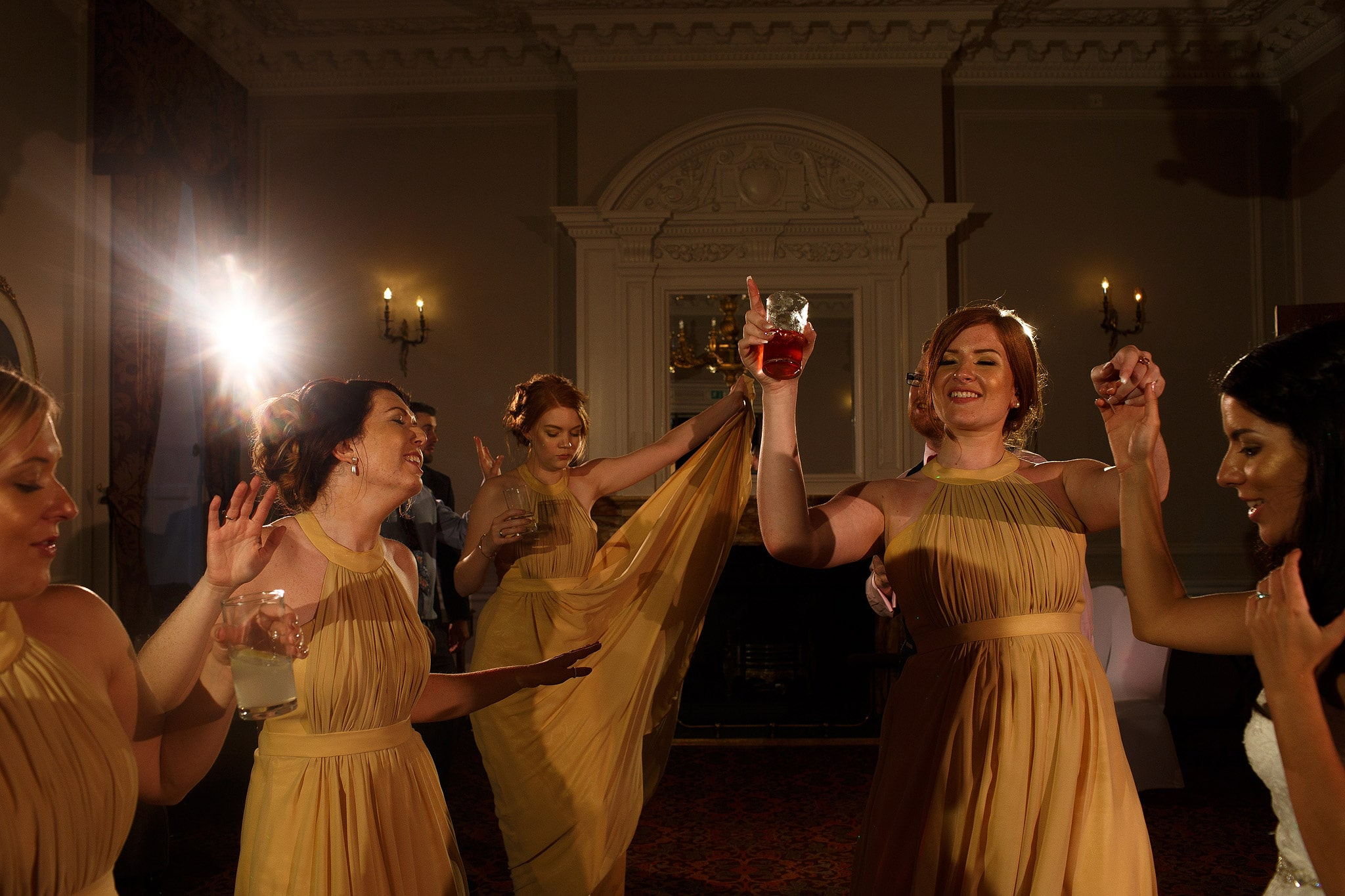 Bridesmaids wearing gold on the dance floor at Crathorne Hall wedding