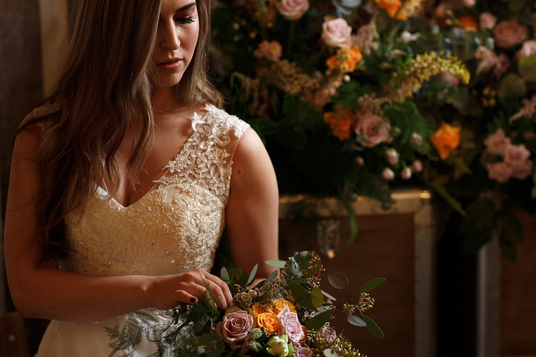 bride surrounded by flowers inside wedding reception at holmes mill