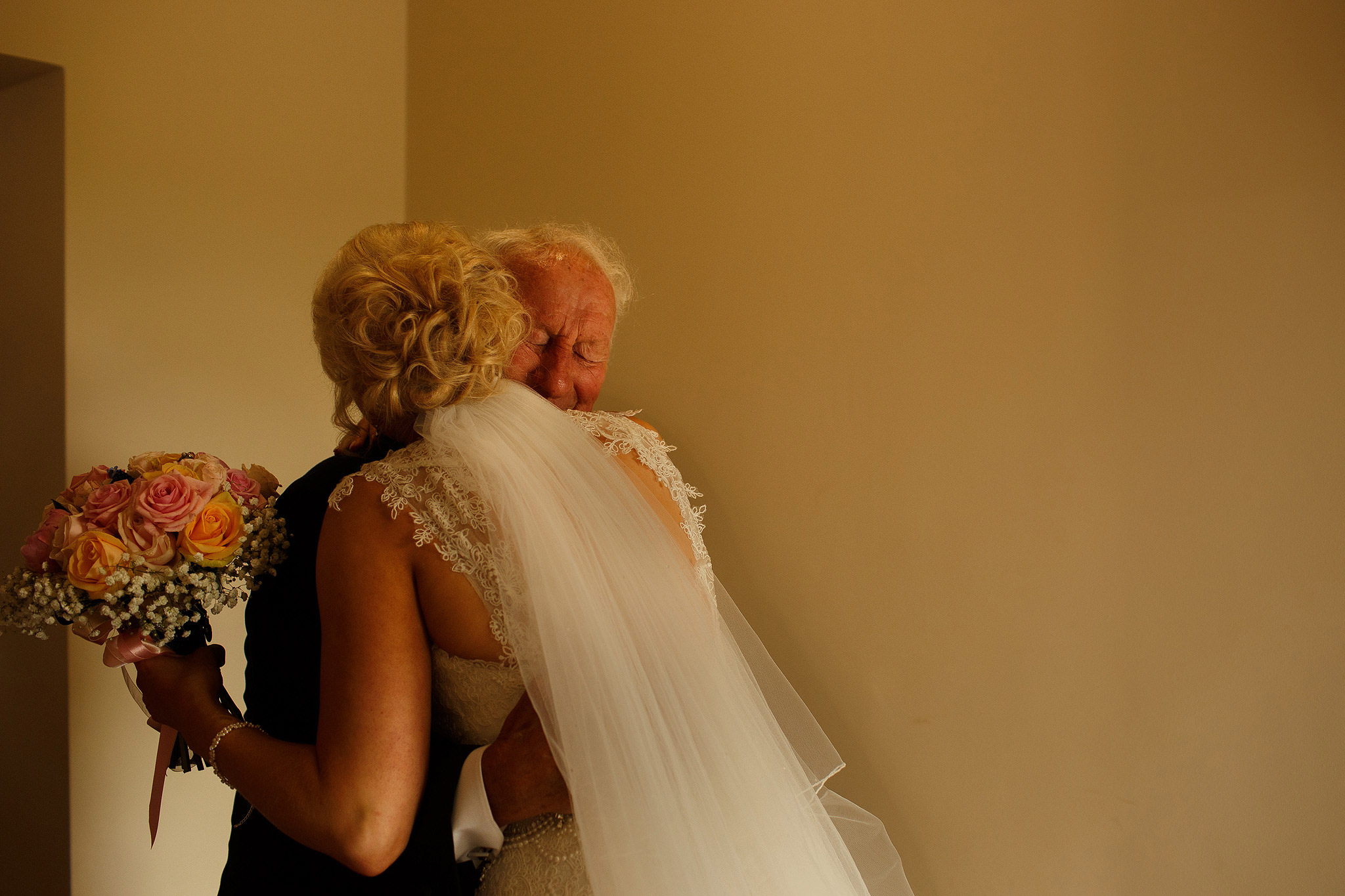 bride hugging grandfather as he feels emotional