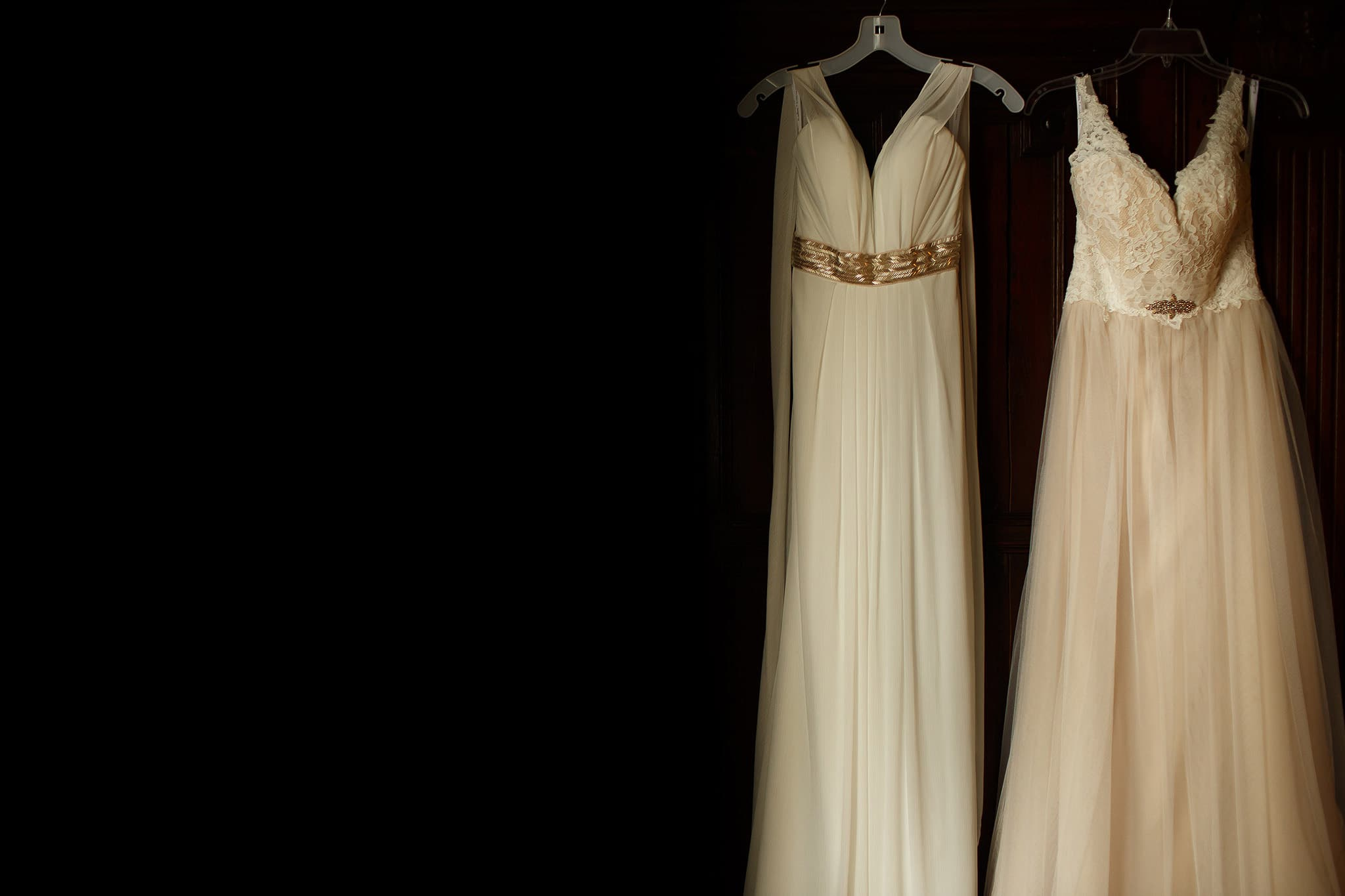 two long brides dresses hung on the wardrobe together - great hall at mains wedding photography