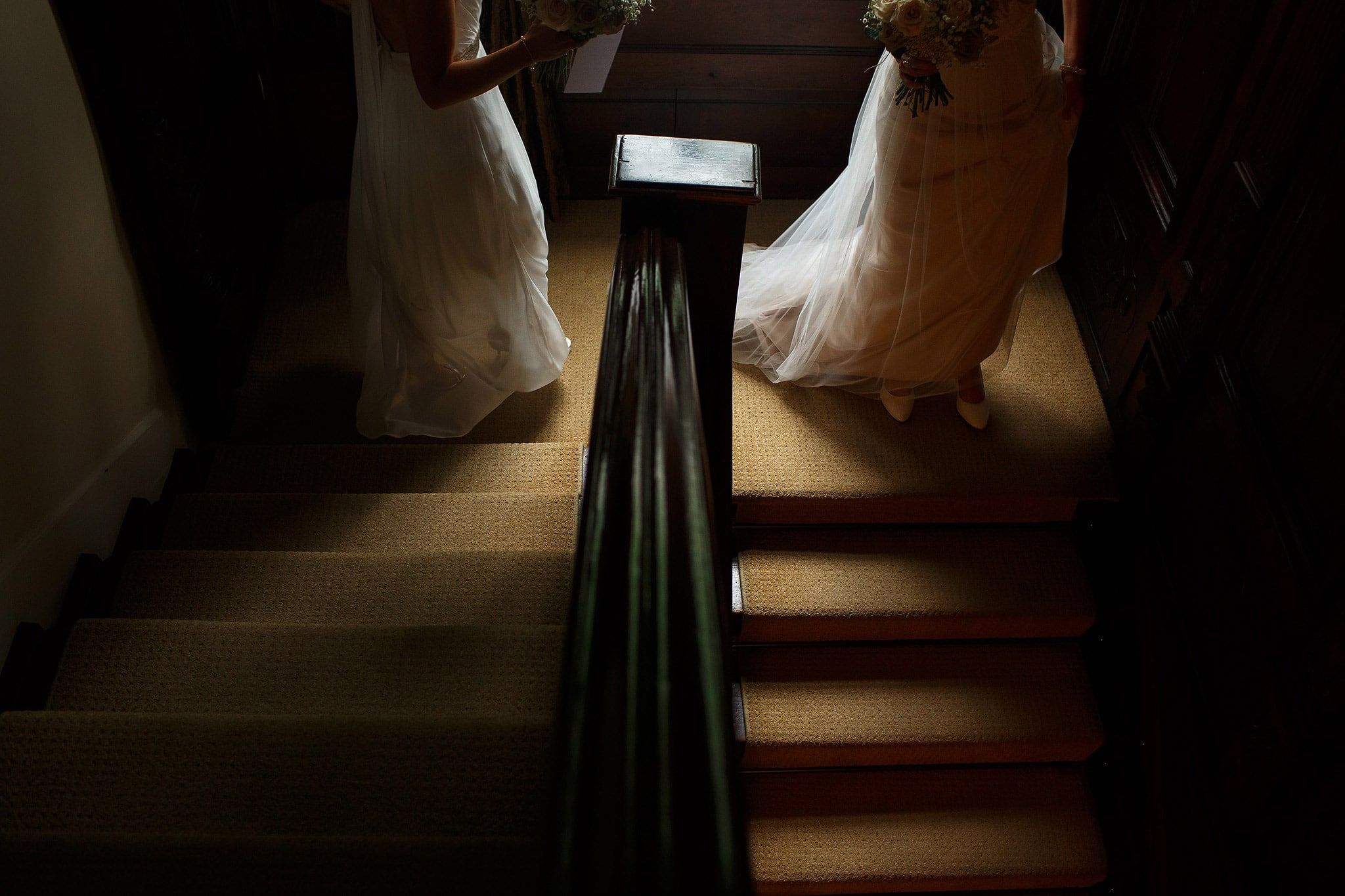 Brides walking down the stairs together inside the house - great hall at mains wedding photography
