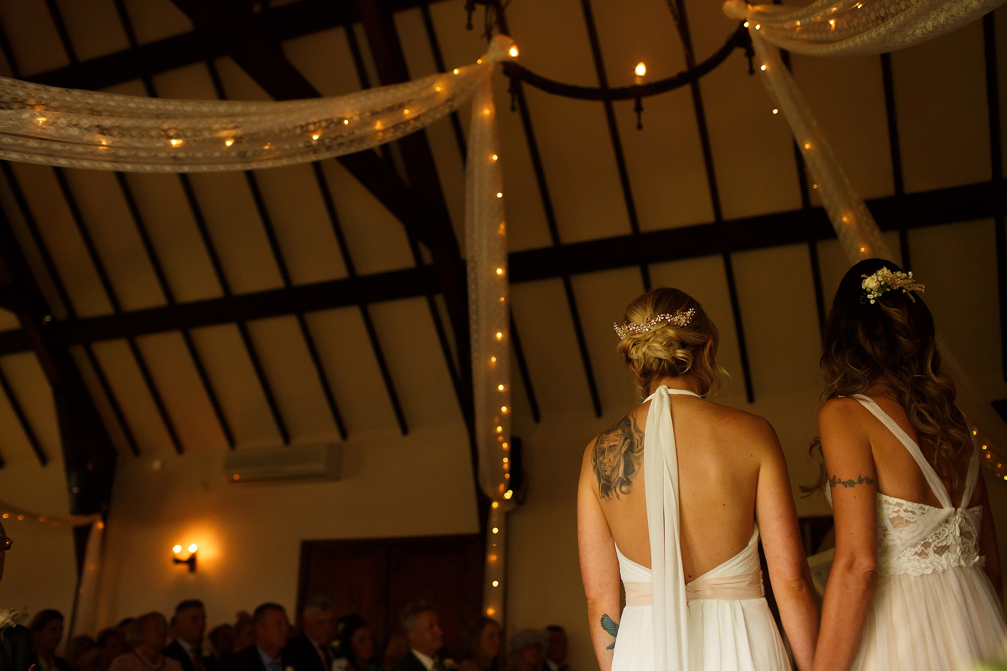 Low angle of the two brides together at the top of the aisle facing their wedding guests - great hall at mains wedding photography