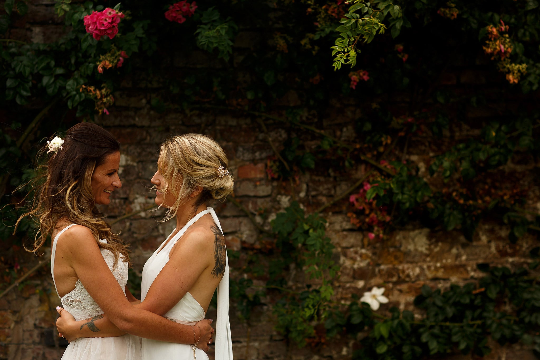 Brides wearing dresses hugging in the gardens at great hall at mains with red brick wall and flowers behind