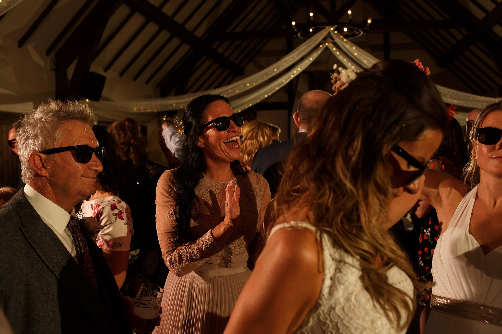 Packed wedding reception as guests dance on the dance floor wearing black sunglasses