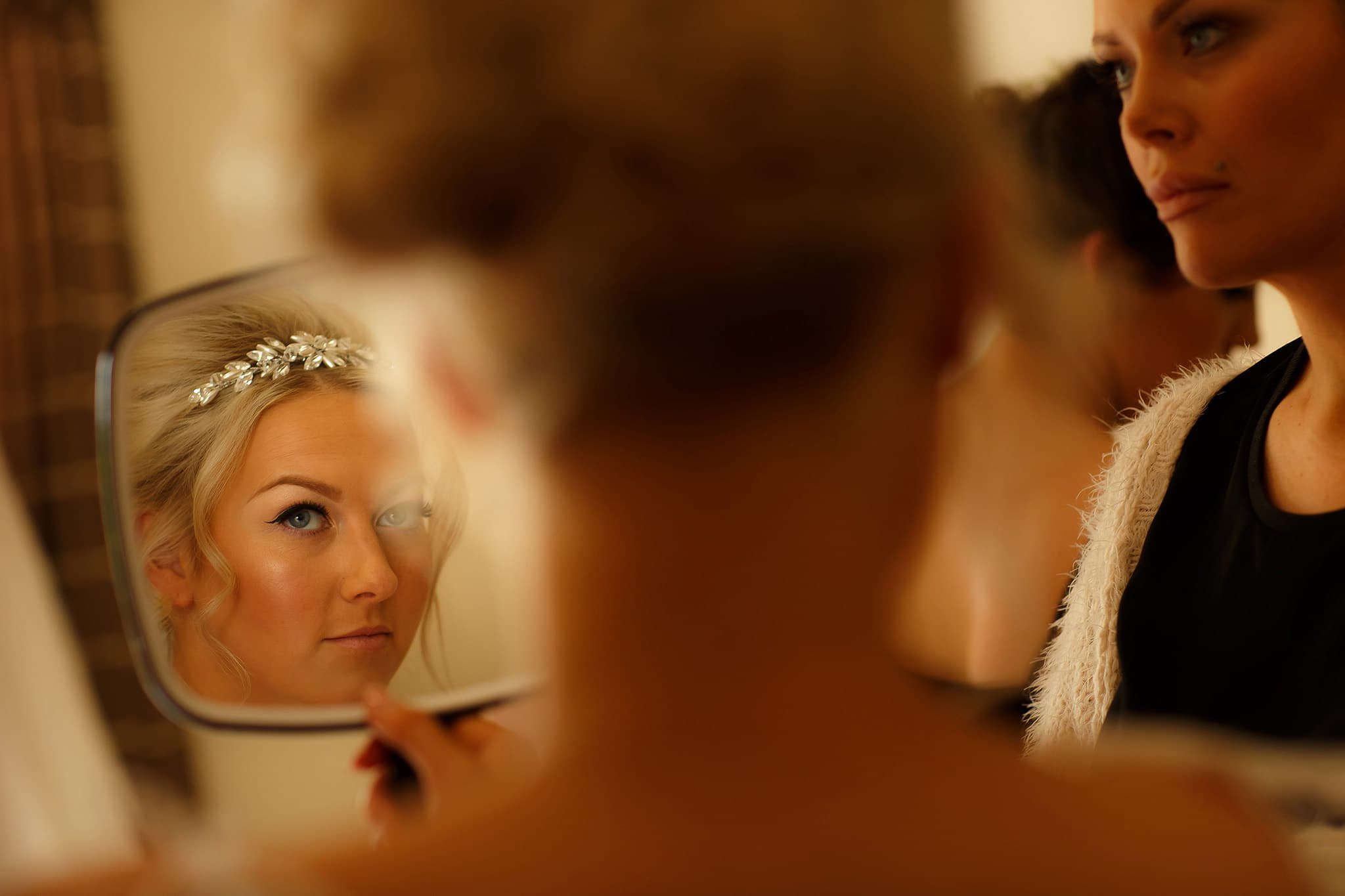 bride looking at herself in a small mirror