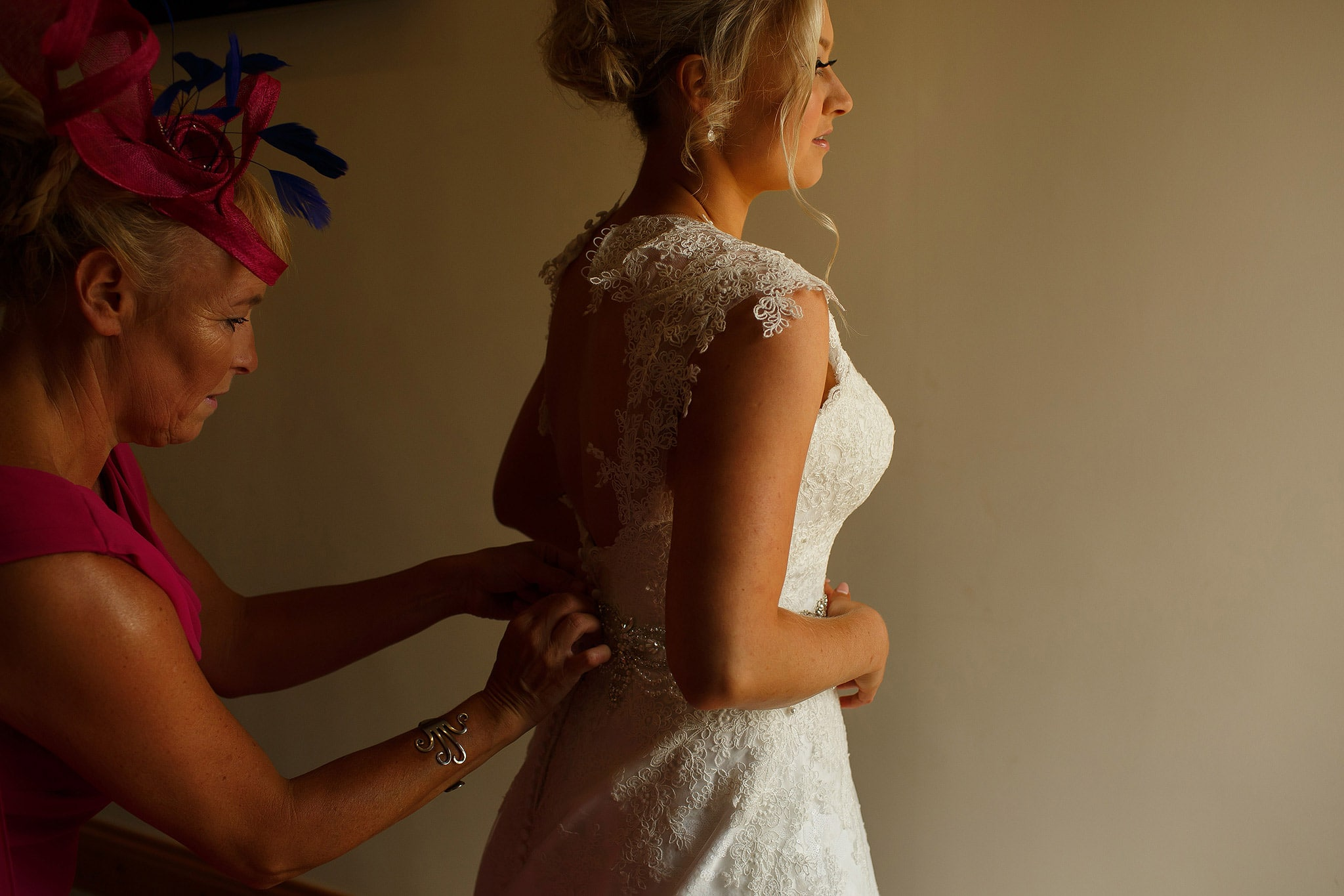 bride having her dress fastened up by mum