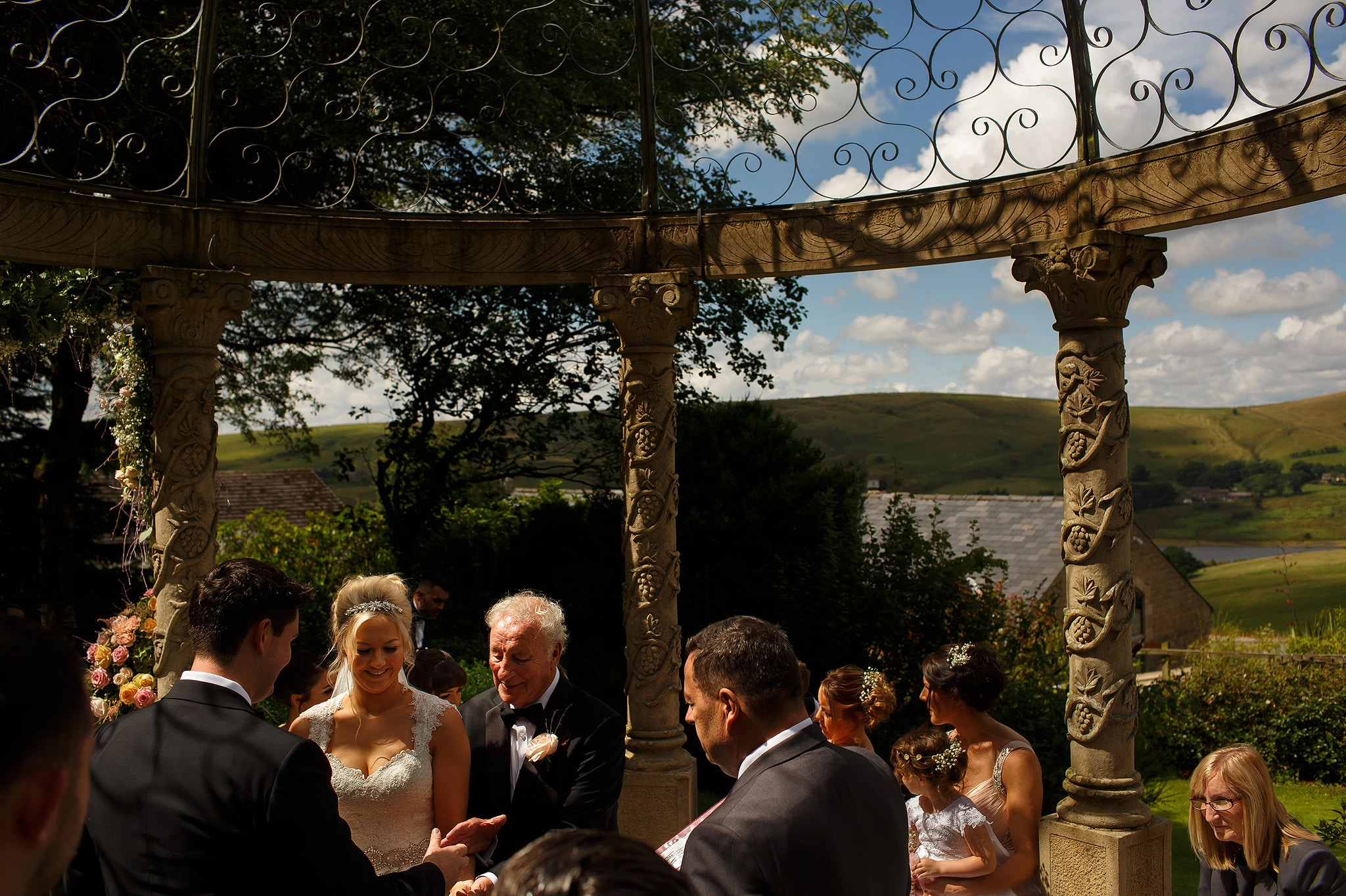 bride arriving at the top of the aisle under arch at saddleworth hotel