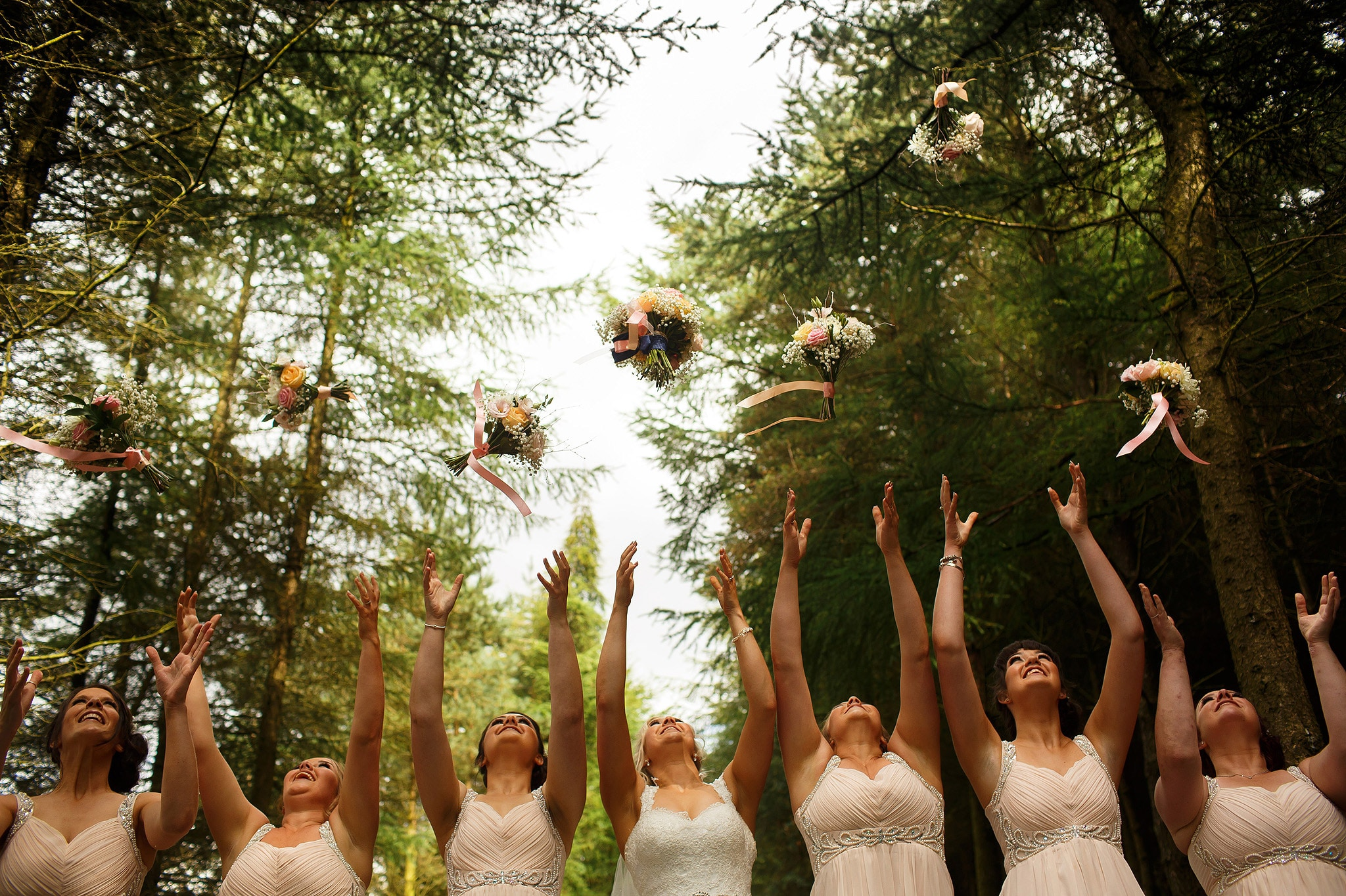Bridesmaids throwing flowers in the air in the forest behind saddleworth hotel