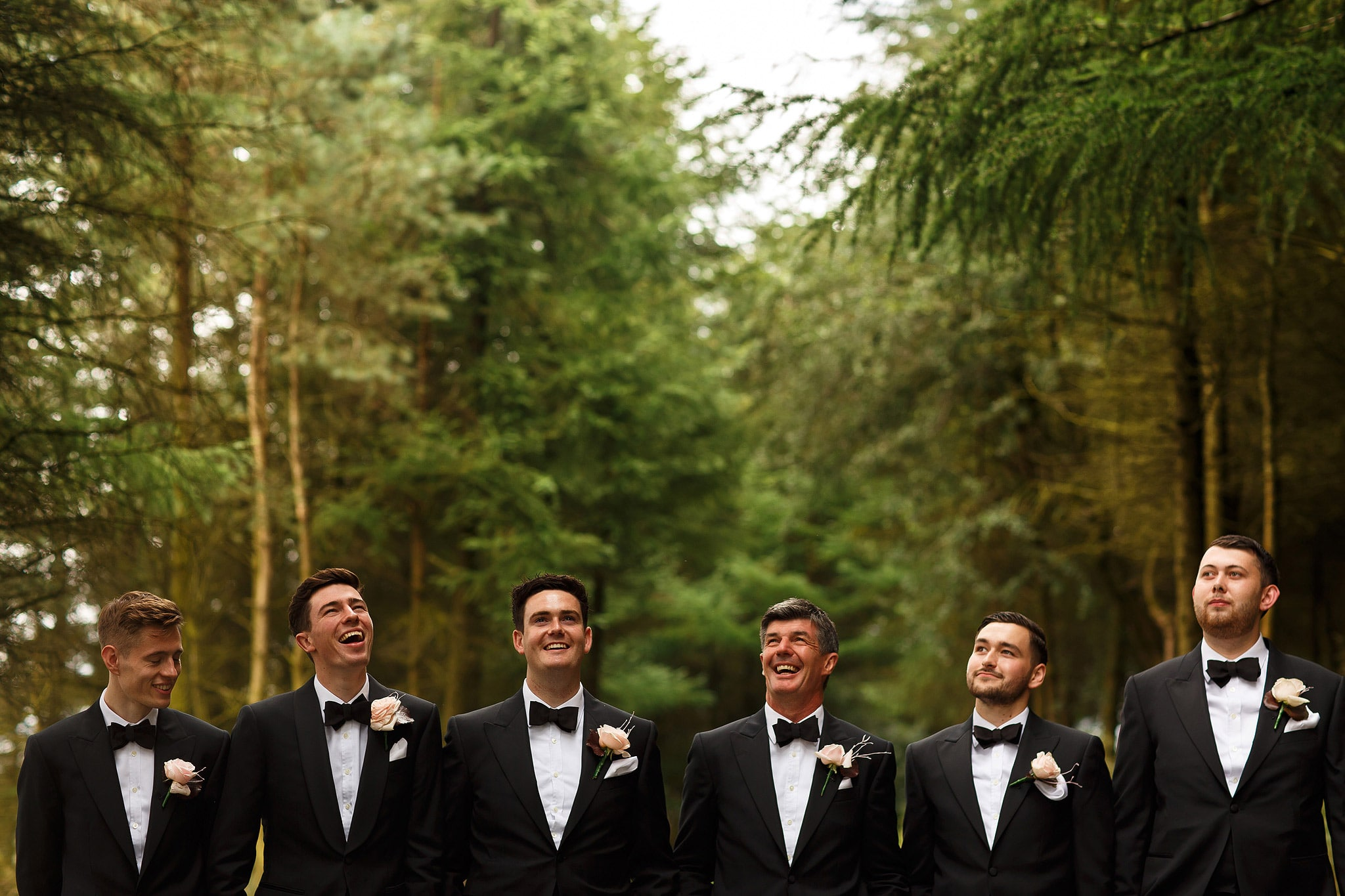 groomsmen wearing black tie suits in the forest at saddleworth hotel