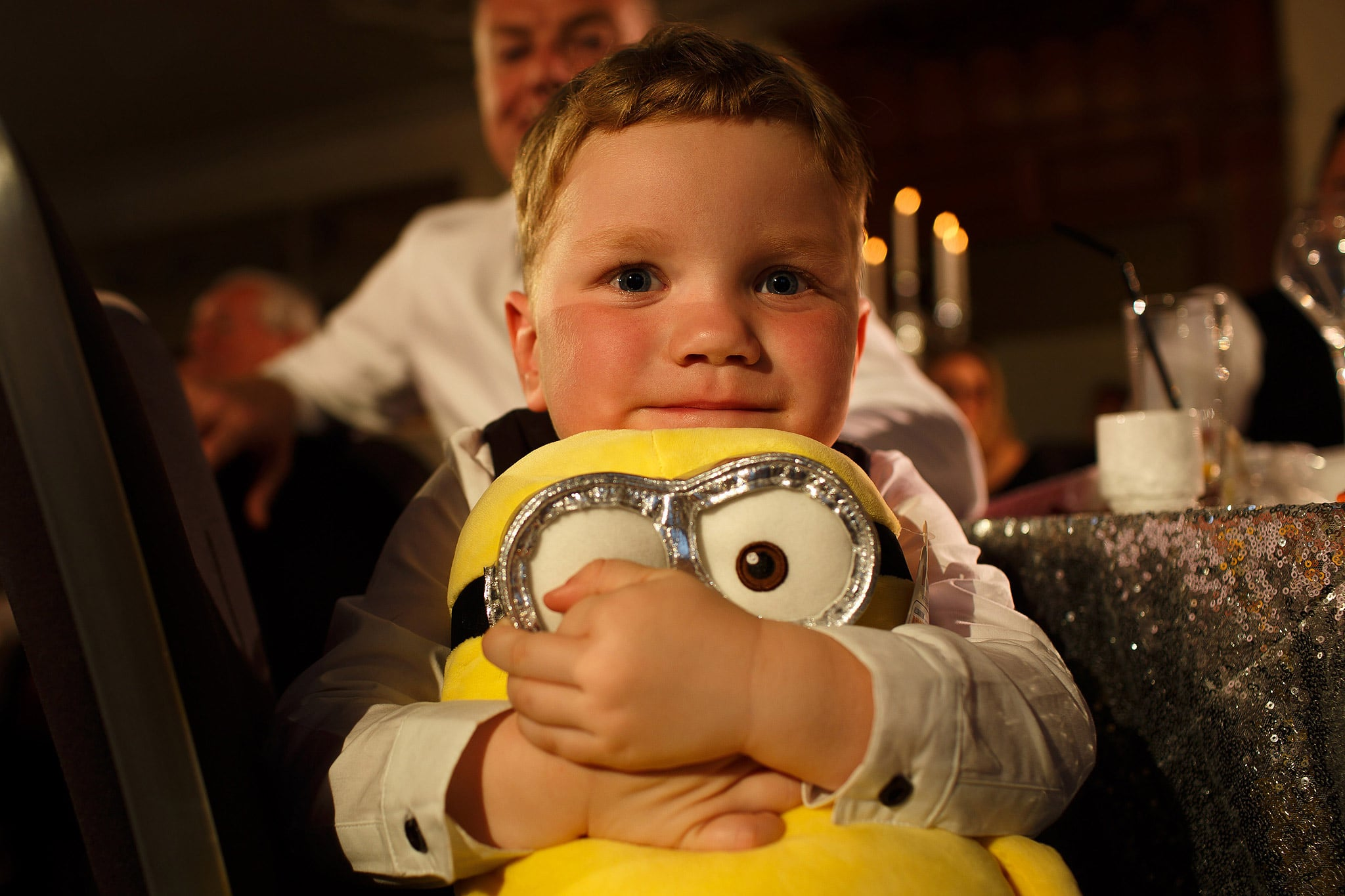 young boy hugging minion teddy at wedding