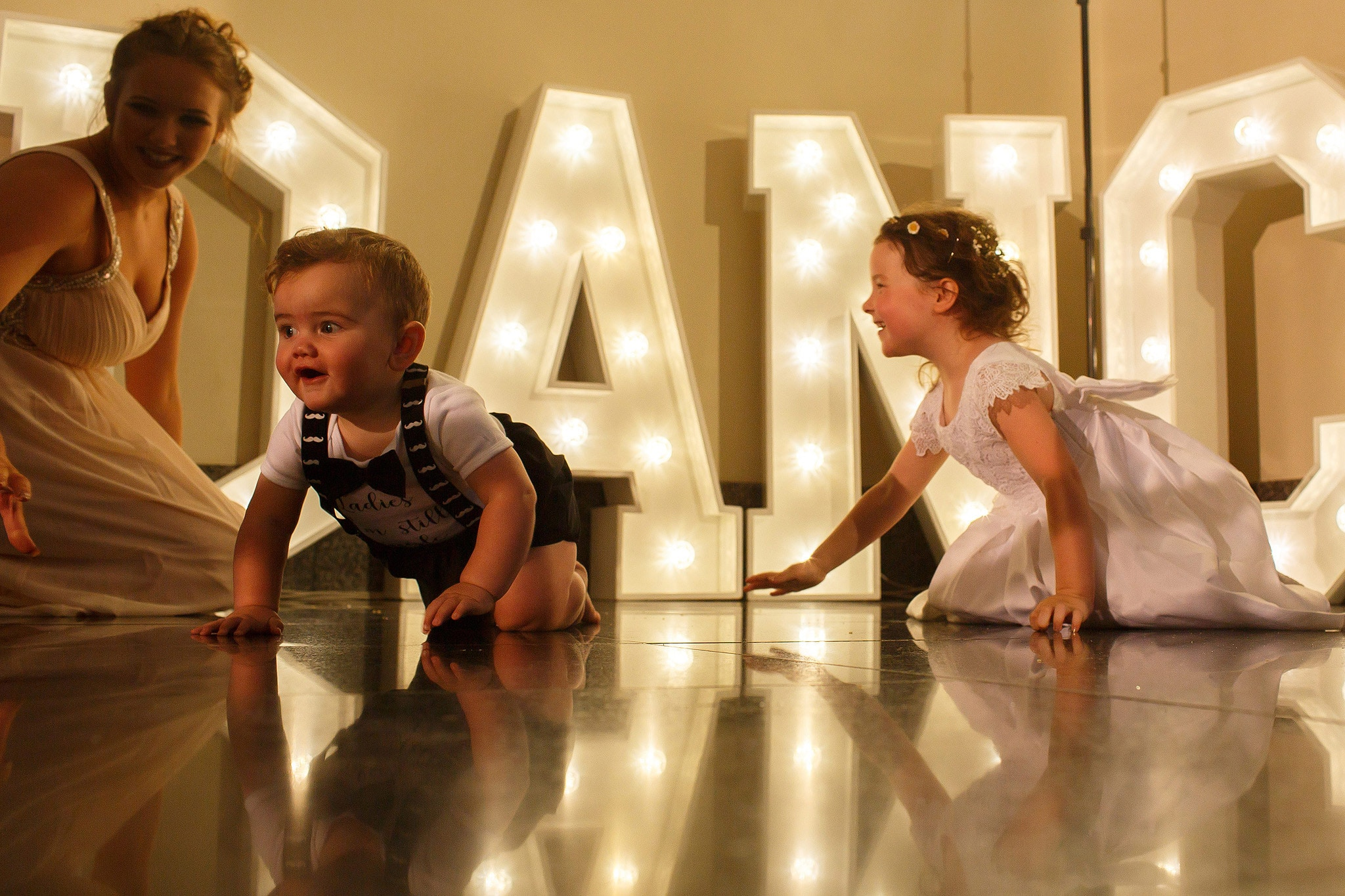 children playing in front of light up letters at wedding reception