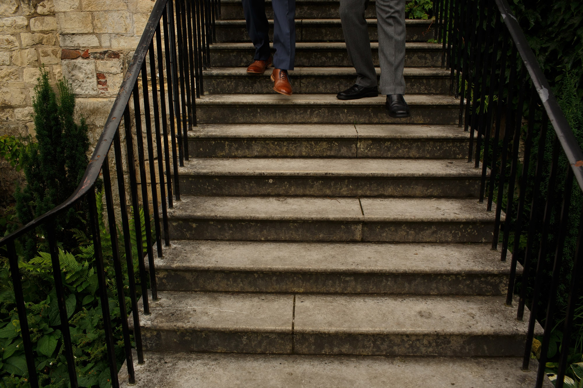 Groom and groomsmens feet as they walk down the stone steps into grays court walled garden