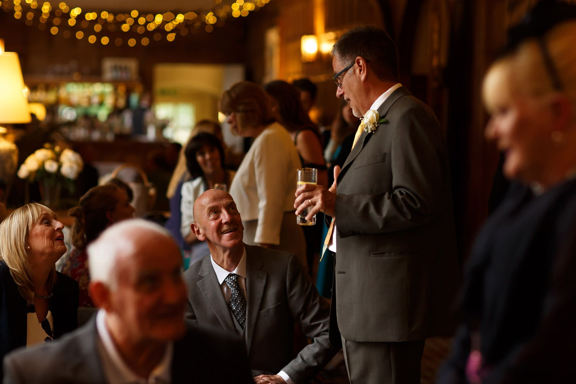 Wedding guests laughing enjoying drinks in the long gallery at grays court wedding