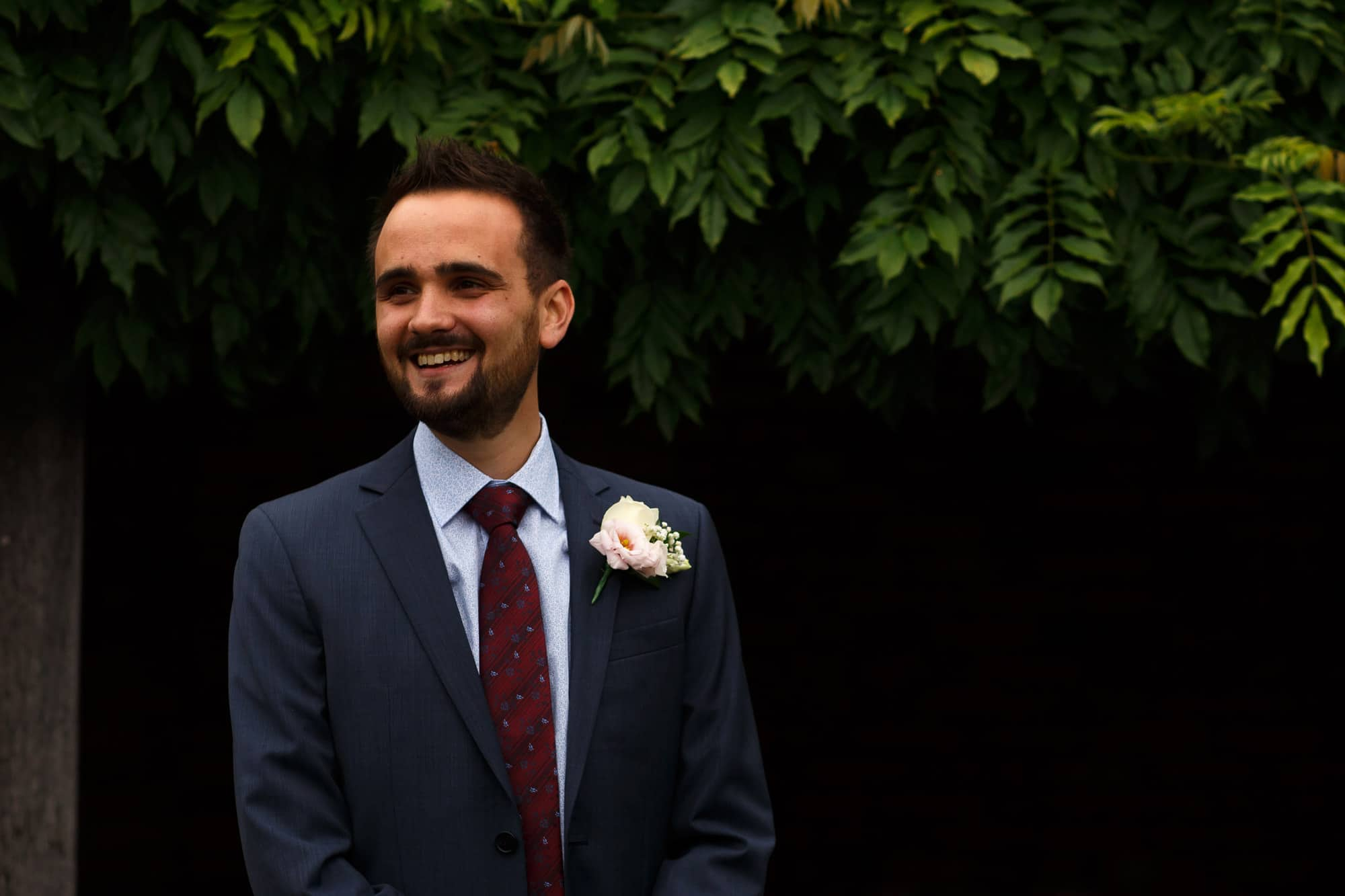 Groom wearing navy suit smiling in reaction to seeing his bride for the first time